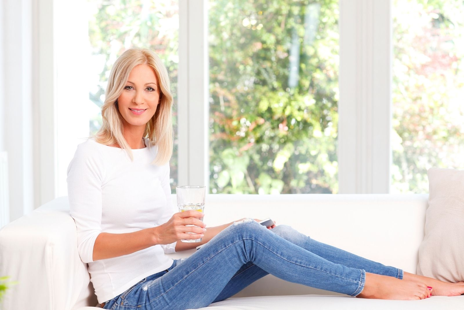smiling mature woman drinking water sitting on the sofa near the windows with feet on the sofa as well