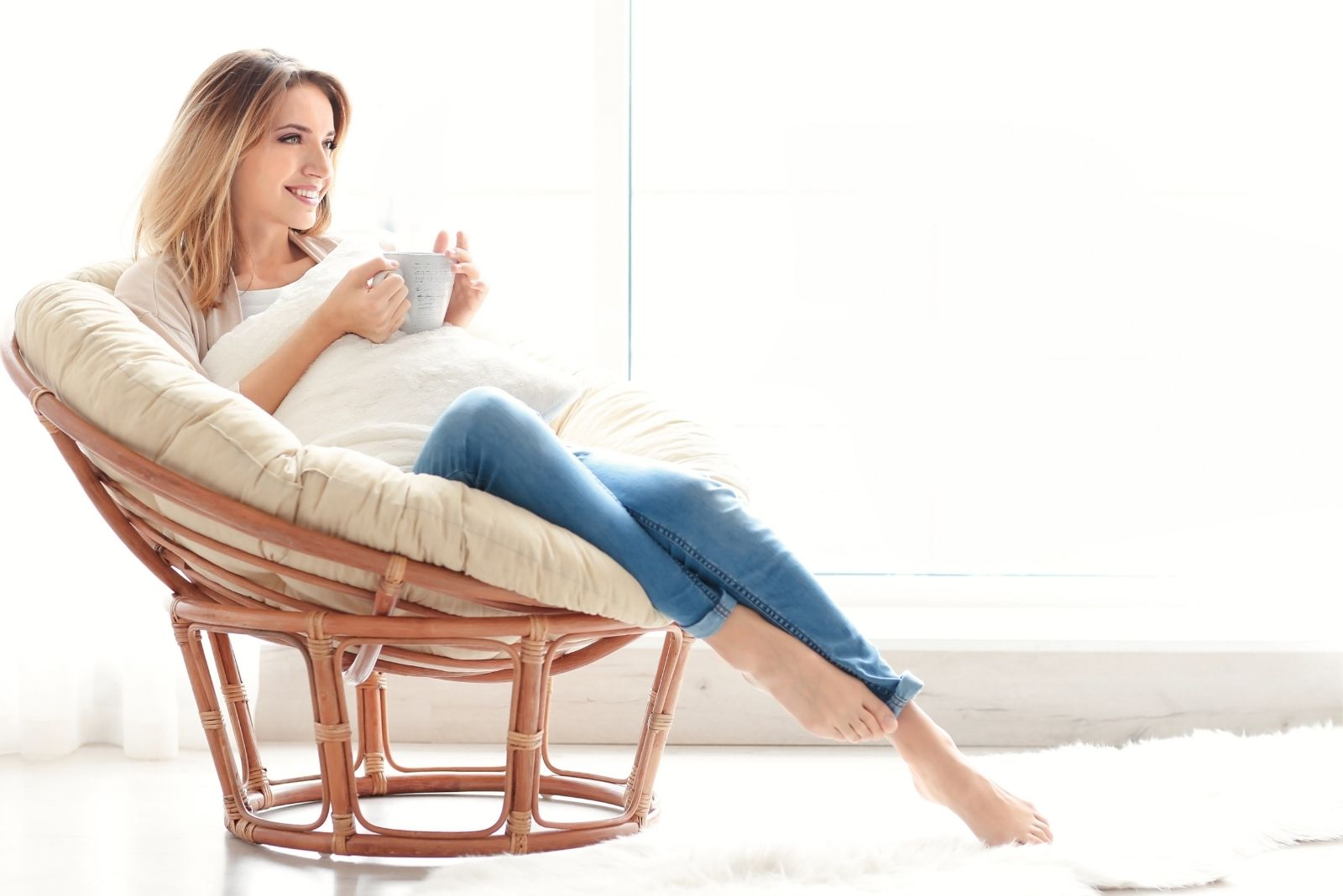 smiling woman relaxing on the comfortable chair drinking coffee near the white curtains