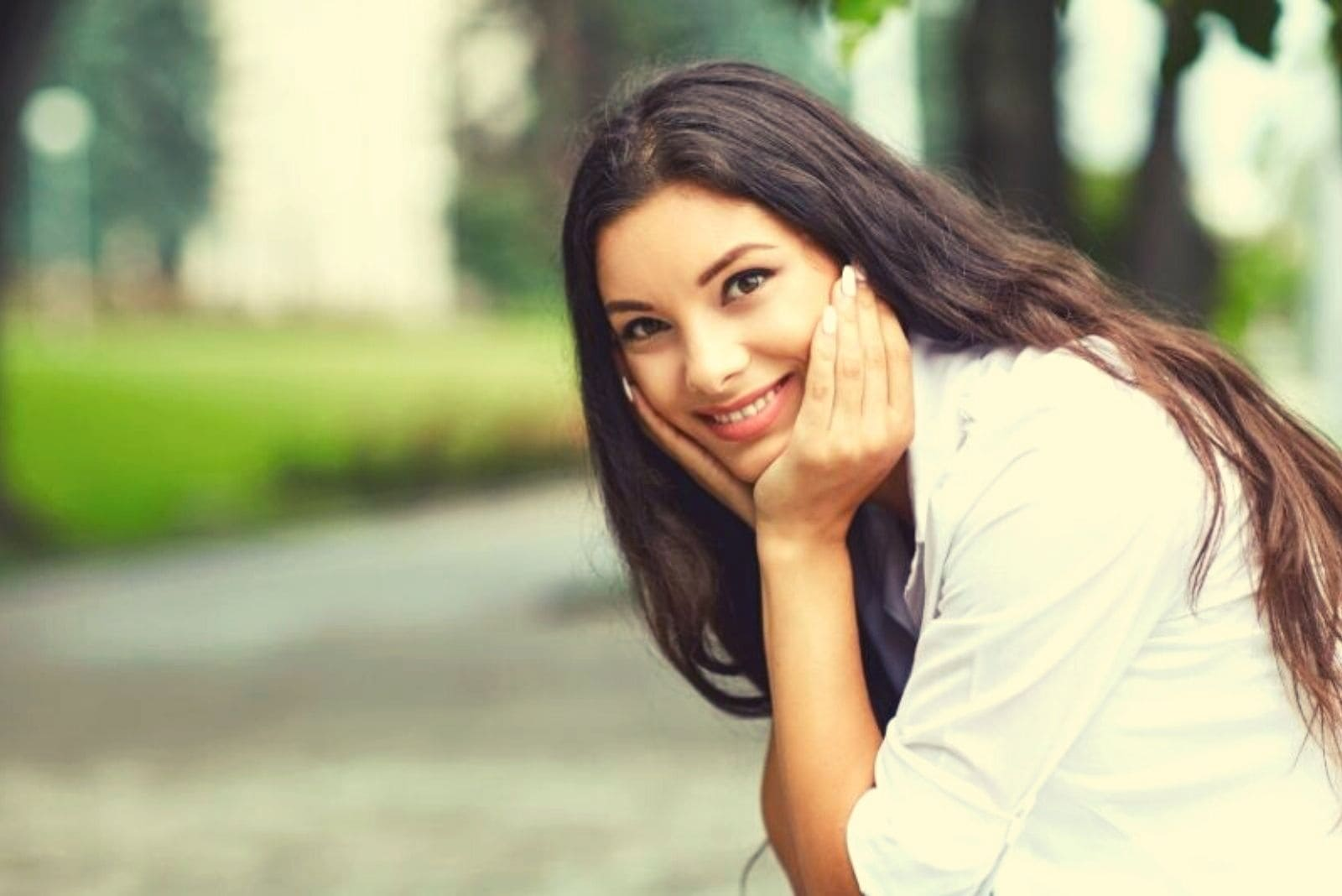 smiling woman sitting at the side of the street with hands supporting her face