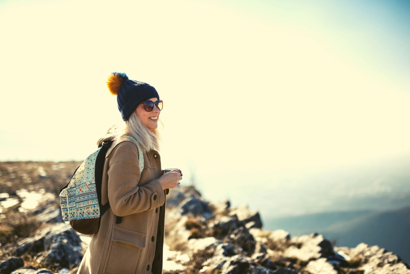 smiling woman standing at the top of the mountain wearing coat and bringing a backpack