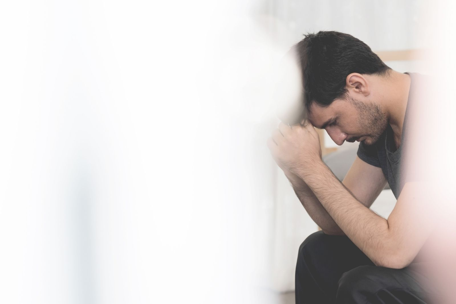 stressed and sad man sitting with image partly covered with white thing