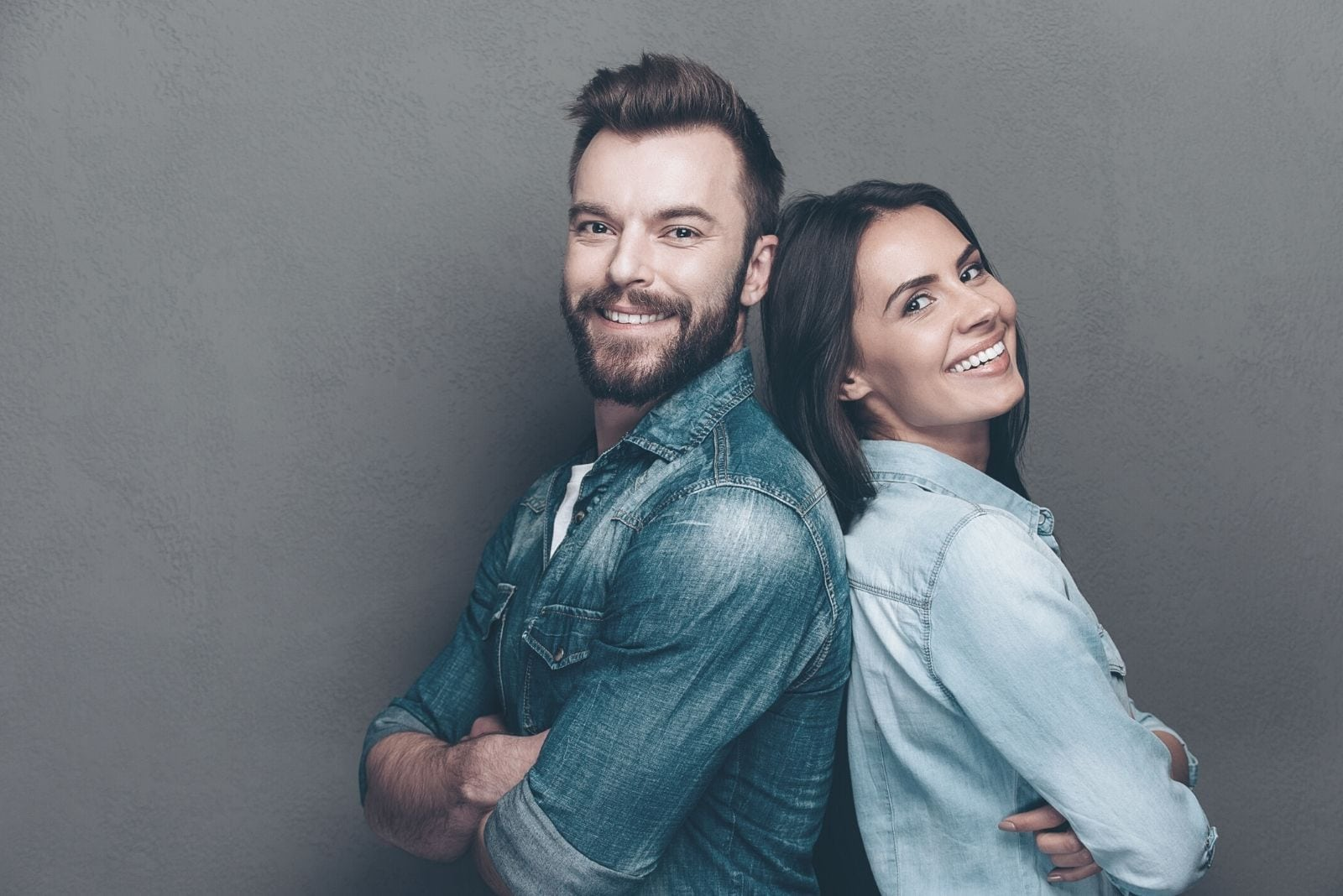 studio shot of a young couple in jeans standing back to back and smiling
