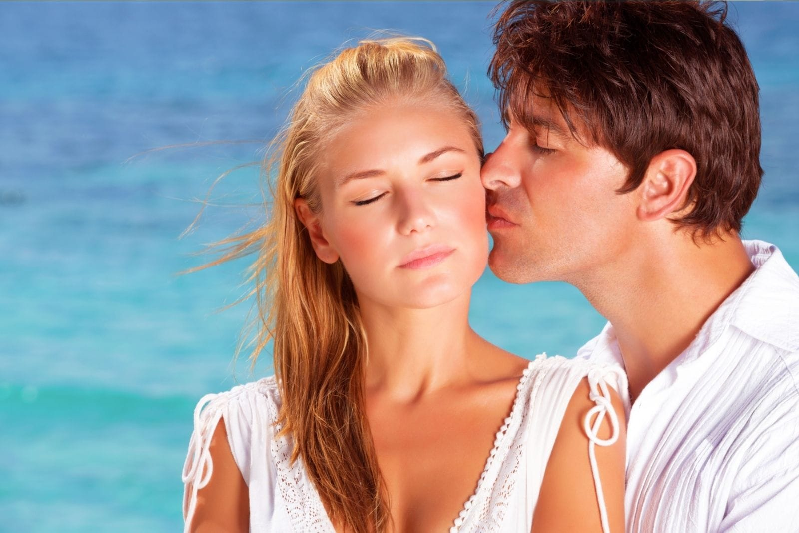 sweet man kissing and hugging a woman standing in the beach