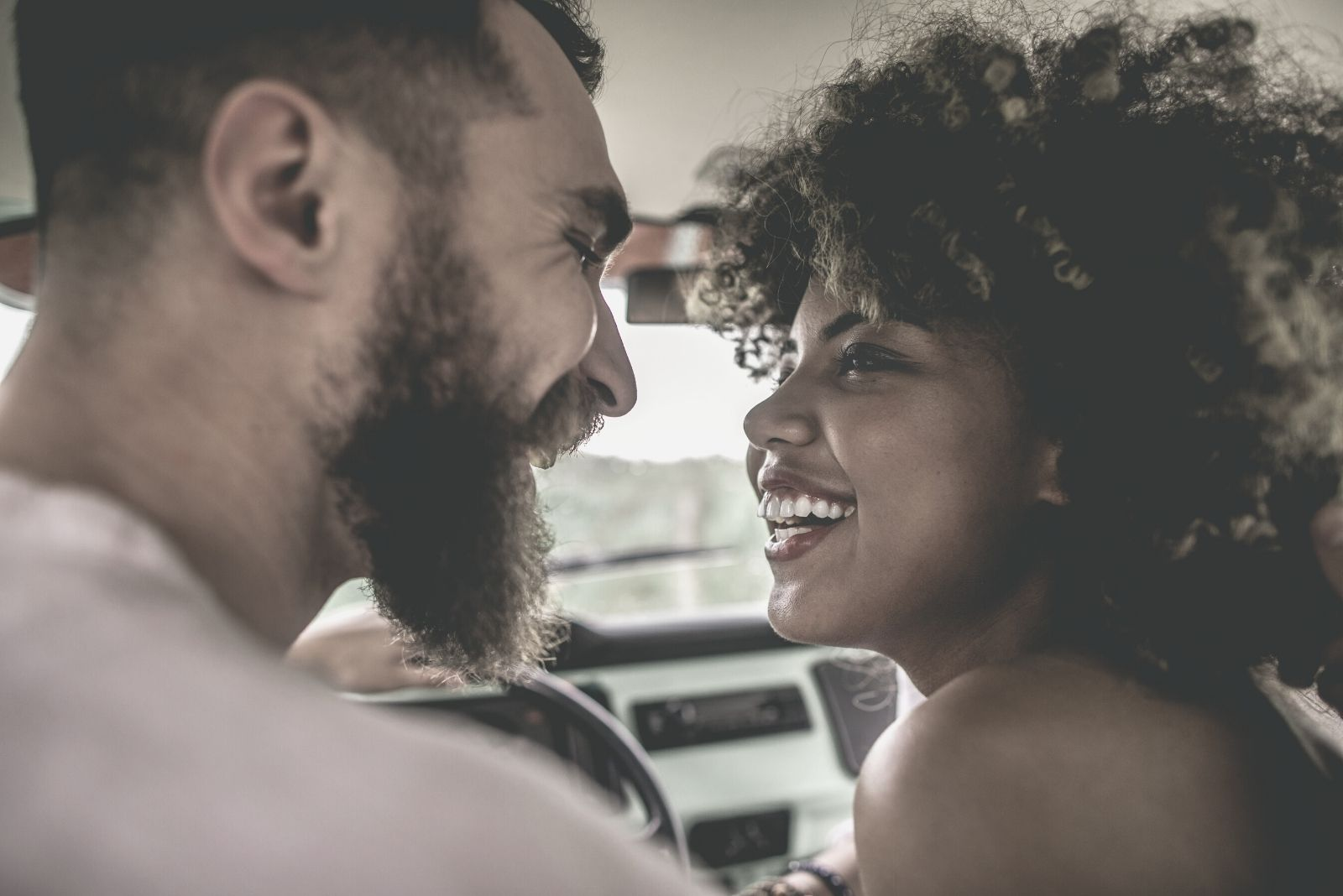 sweet young couple looking eye to eye while inside the car driving