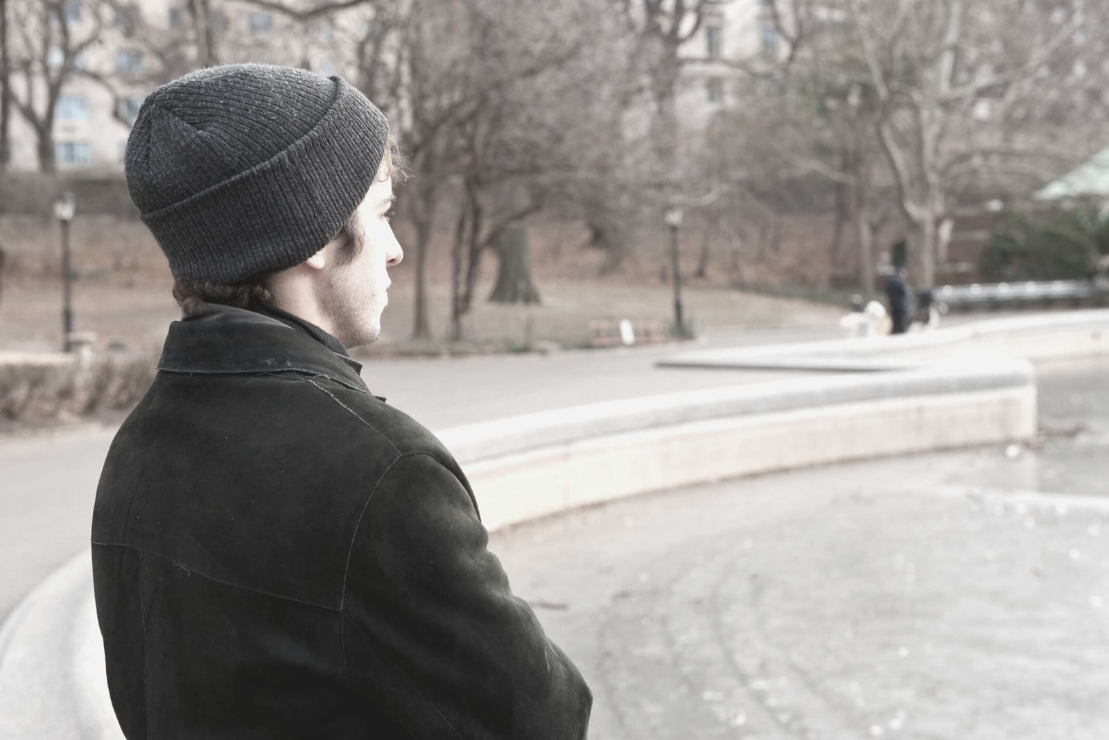 thoughtful young man standing at the central park new york city