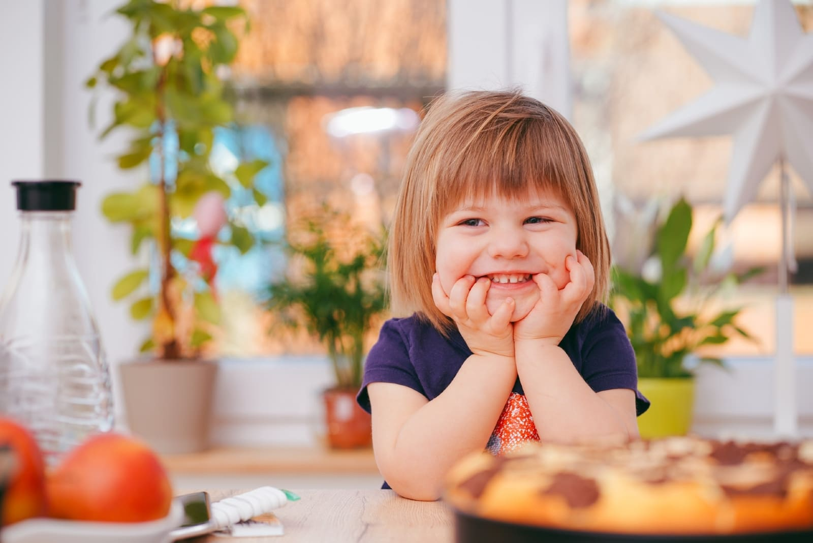 toddler smiling while sitting at table