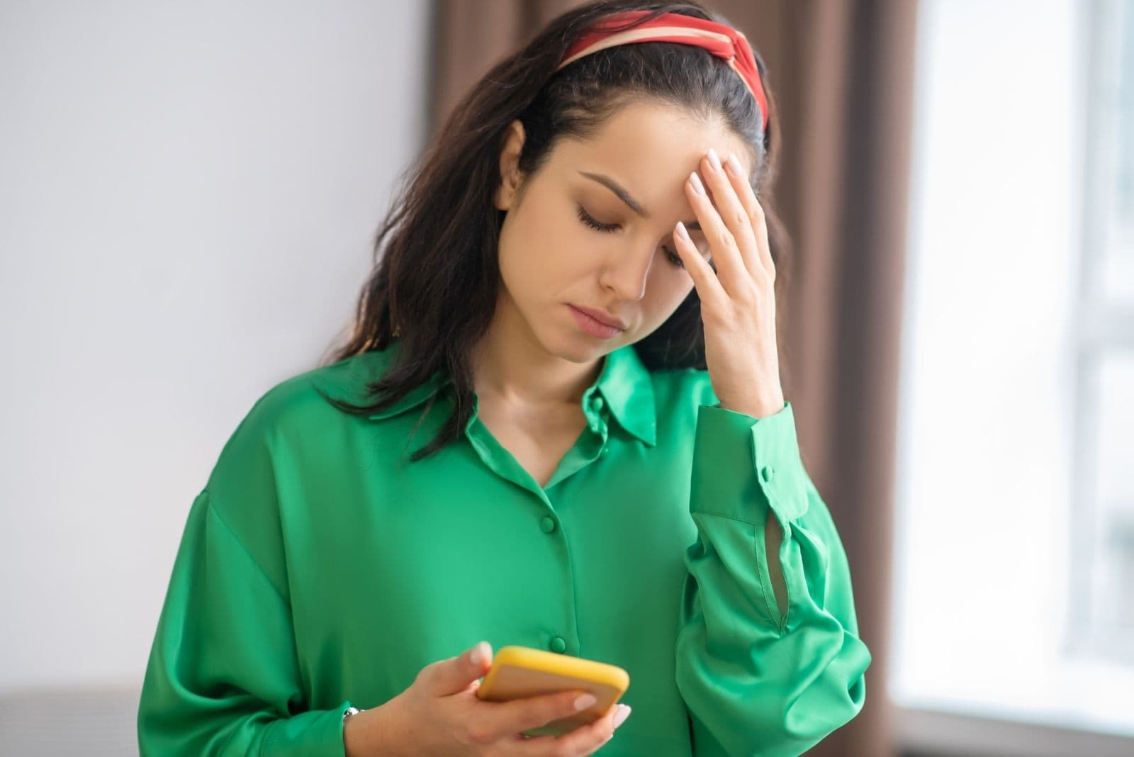 upset woman looking at the smartphone while standing inside home