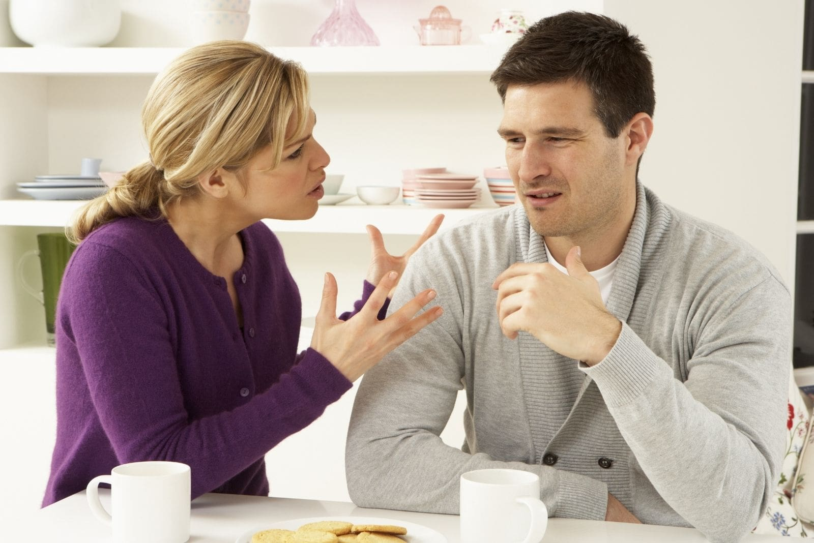 upset woman nagging on man sitting by the table in the kitchen