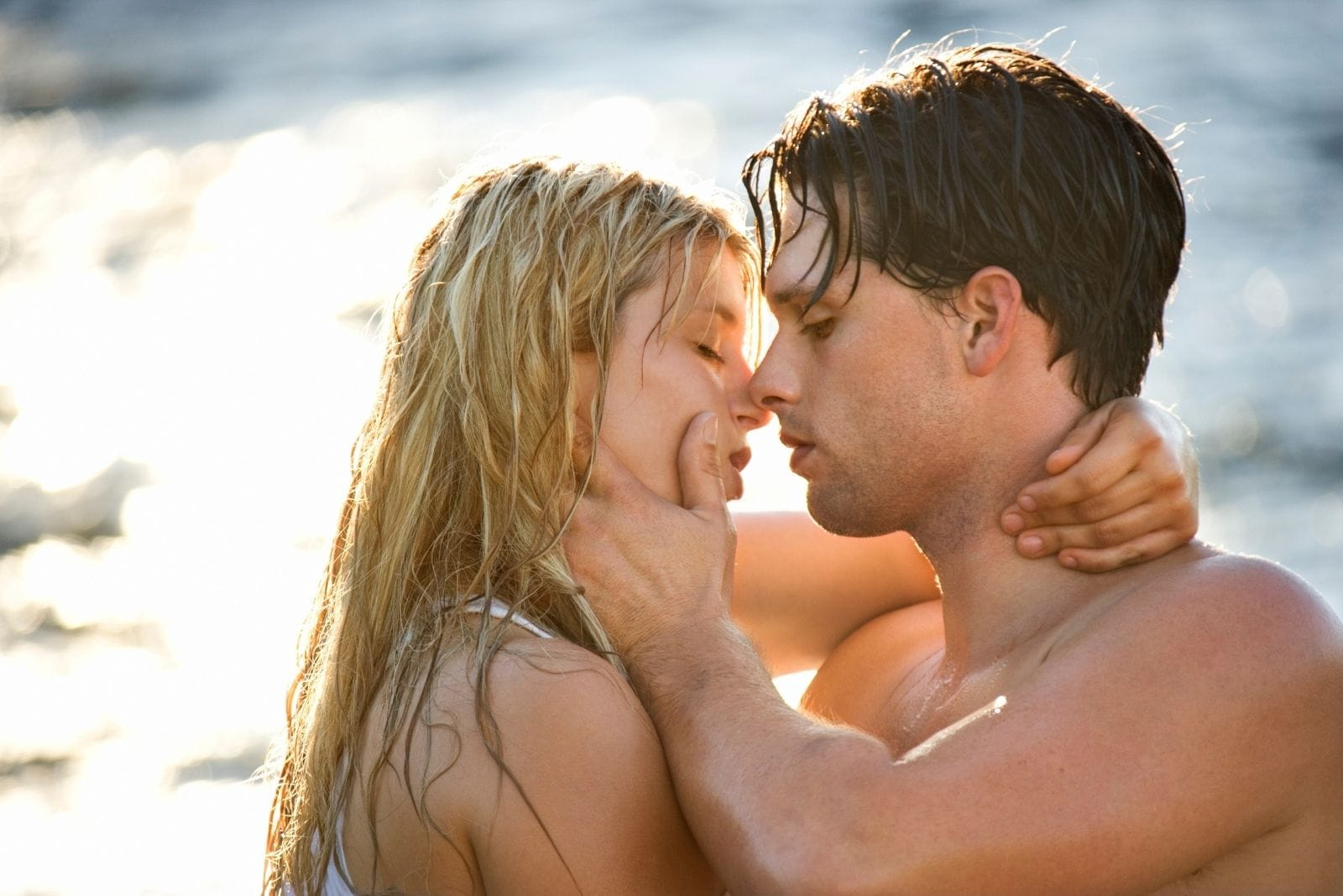 wet couple kissing in the beach with man gently grabbing woman's face