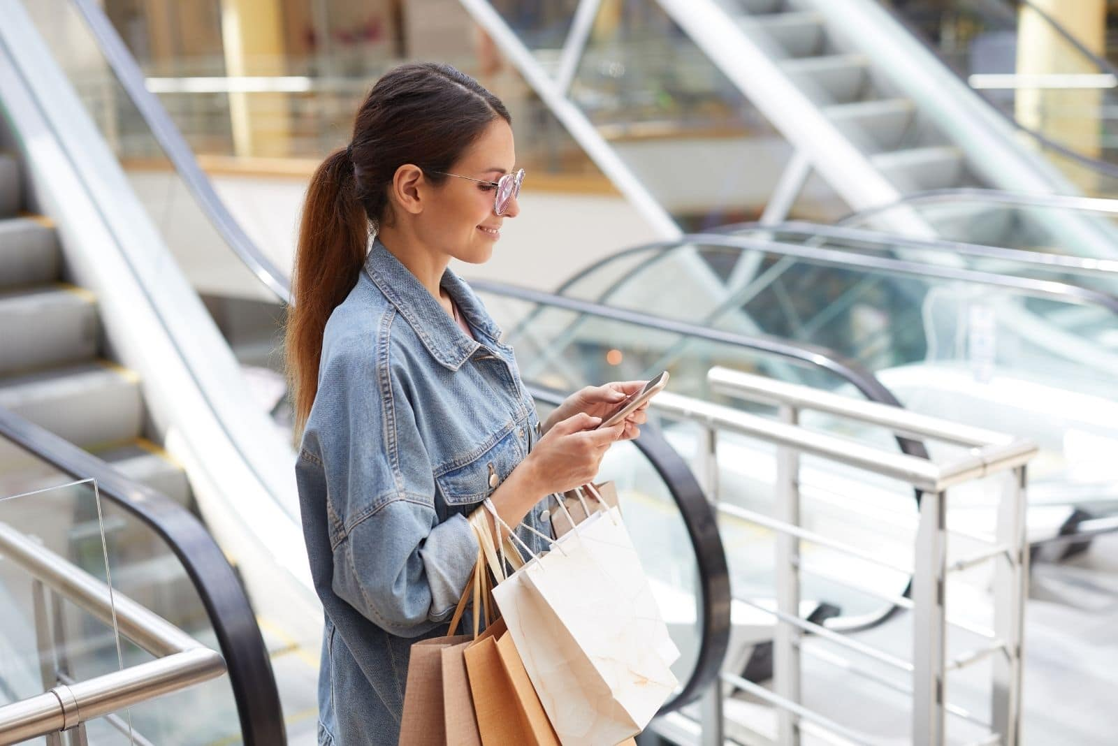 woman at the mall checking on her phone and smiling