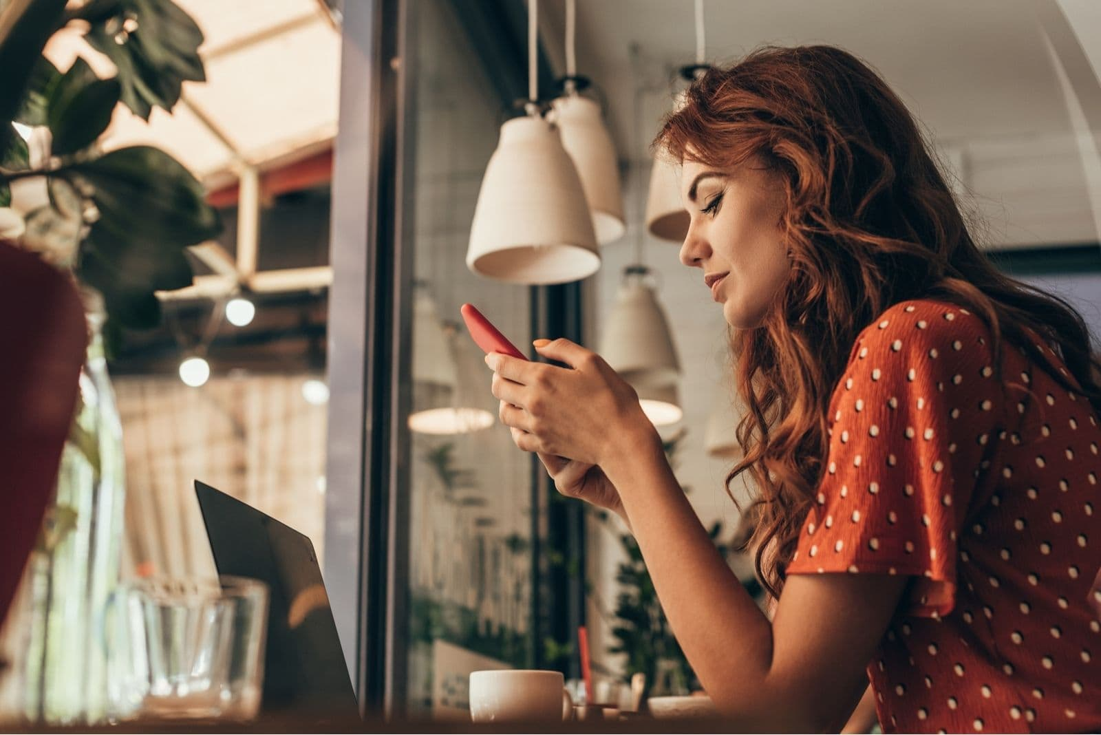woman busy looking at her smartphone in sideview sitting inside a cafe