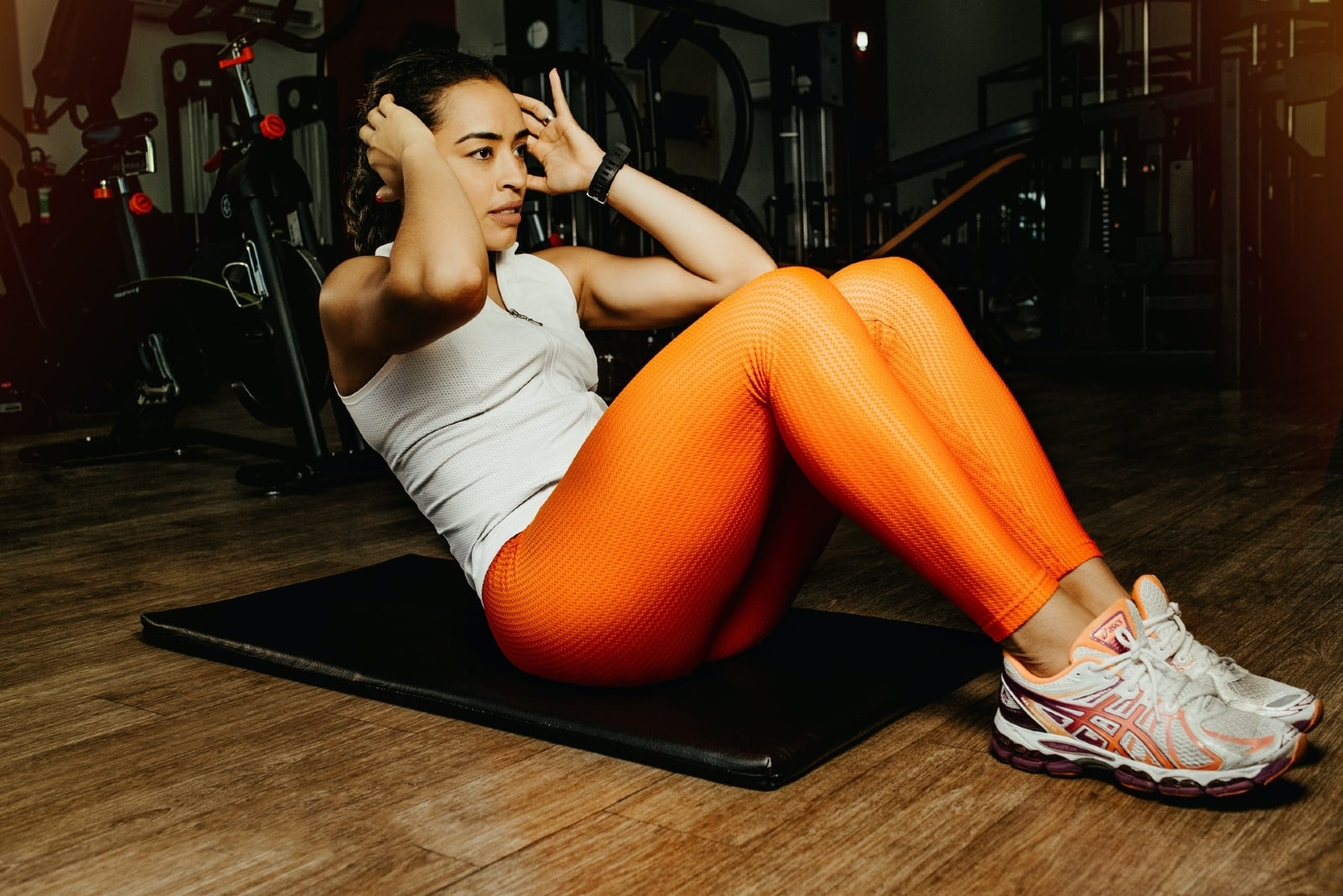 woman in orange leggings doing sit ups in gym