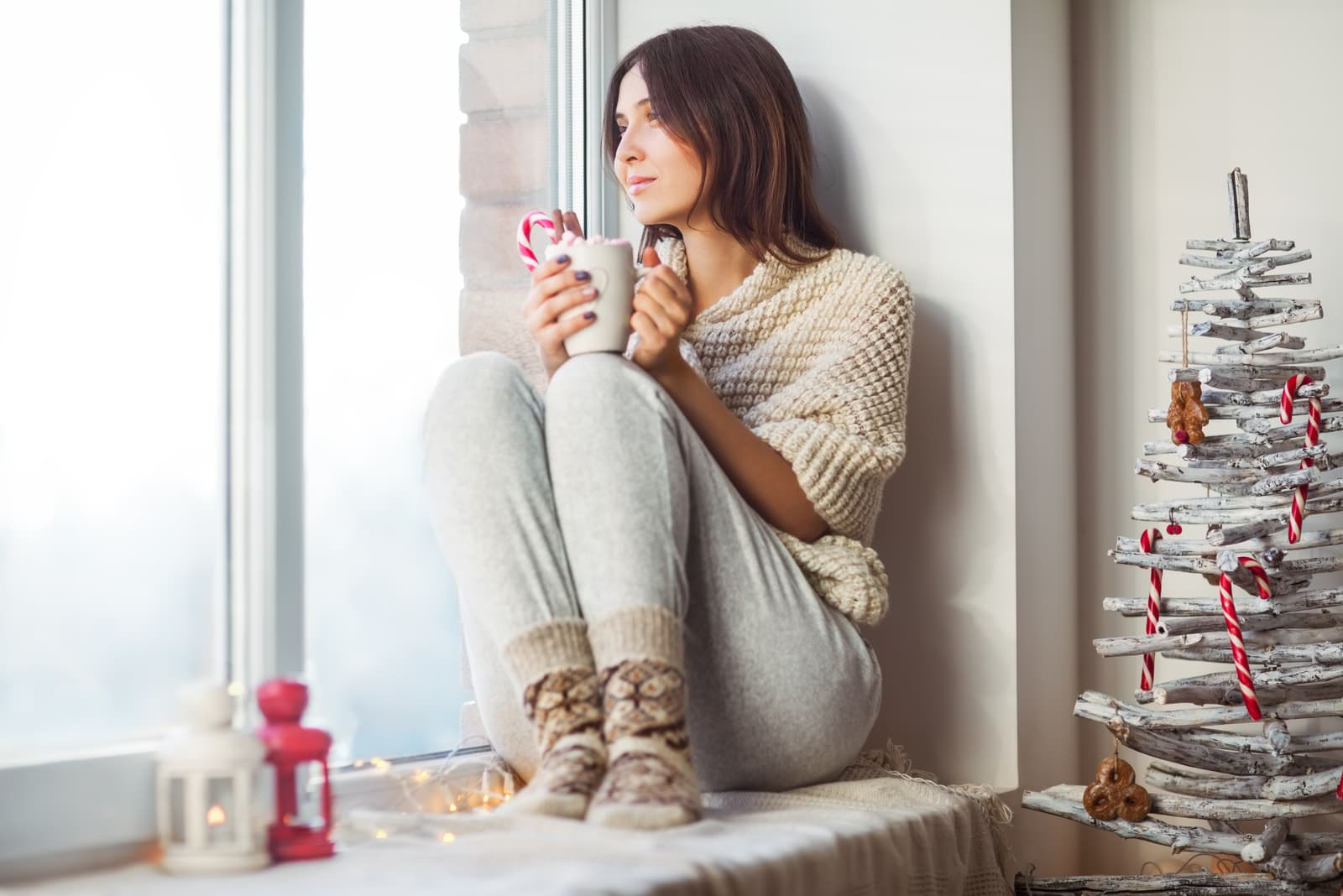 woman drinking hot coffee sitting on window sill
