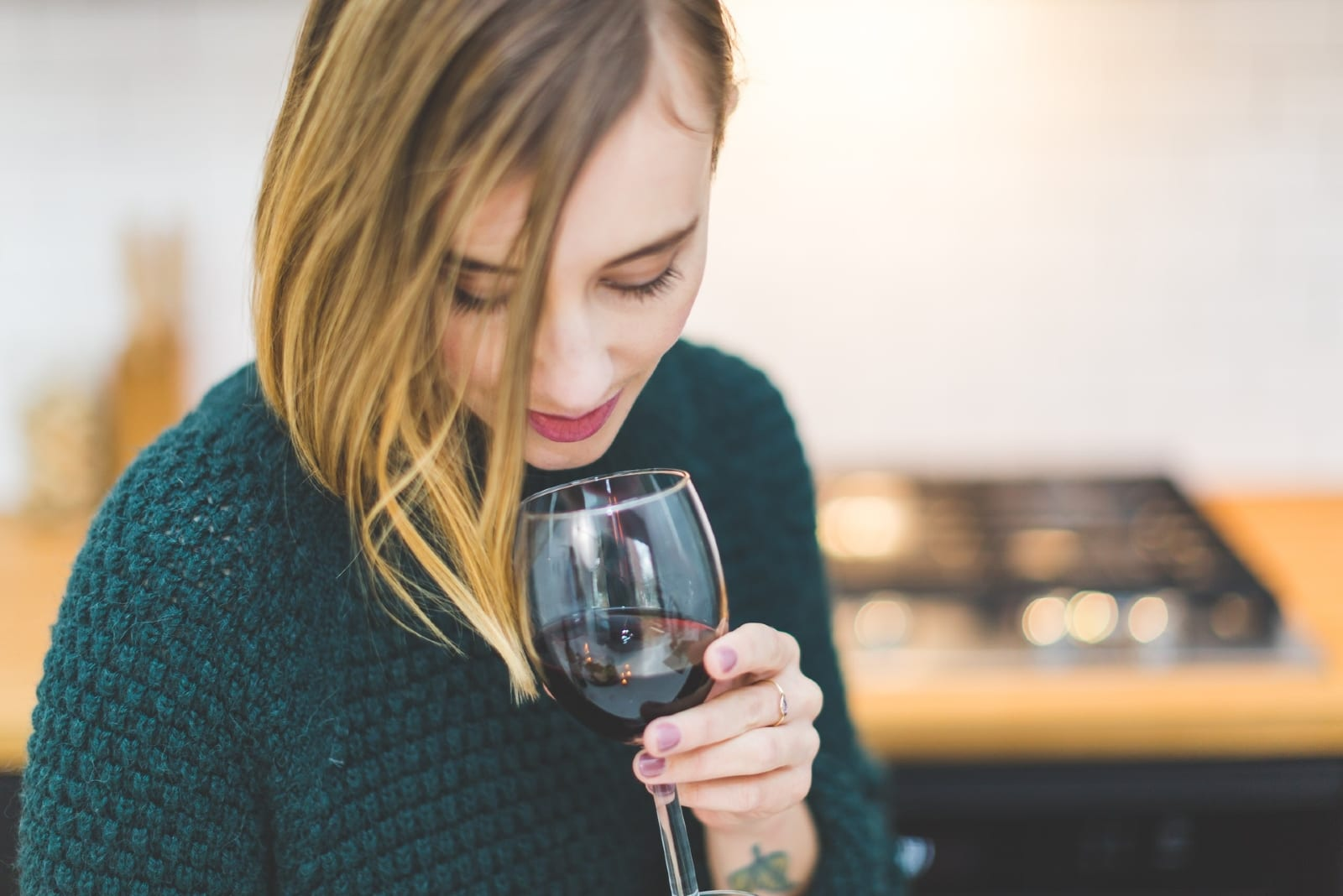 woman in green sweater drinking wine