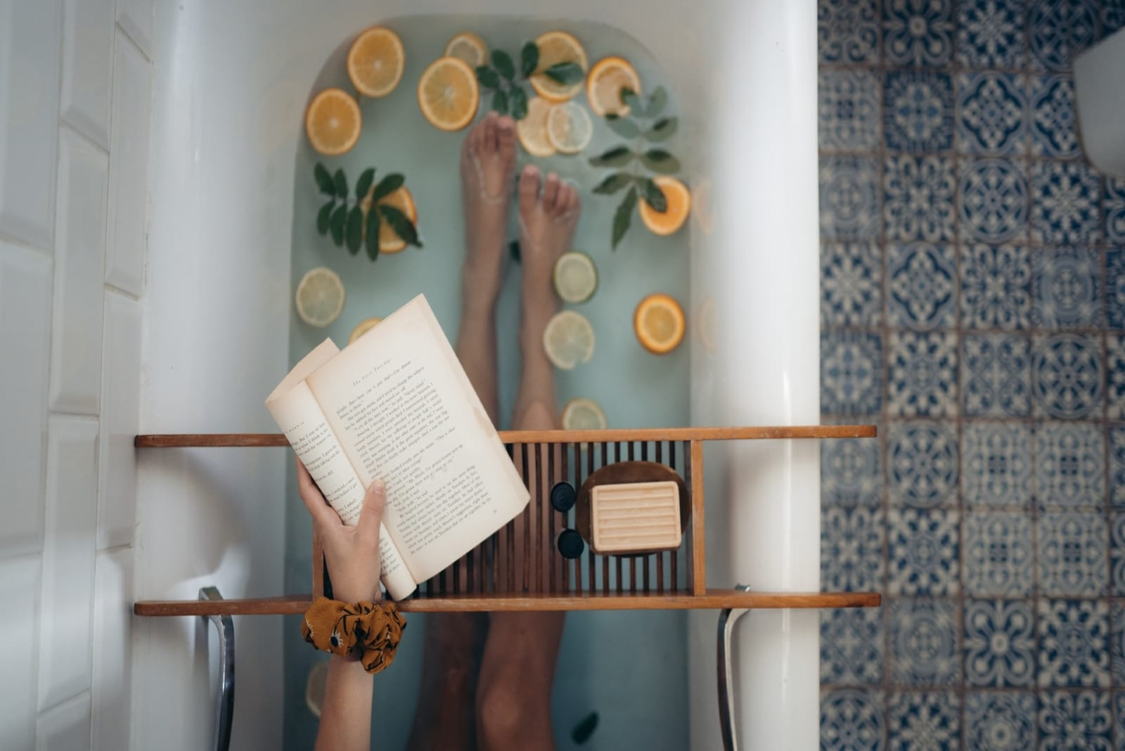 woman holding open book while sitting in bathtub