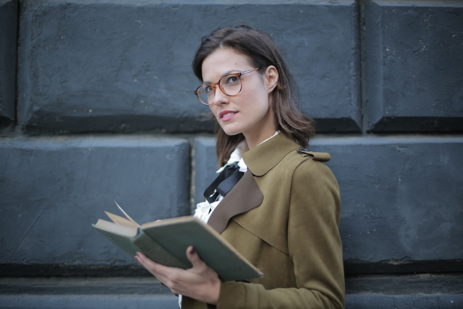 woman with eyeglasses holding open book while standing near wall