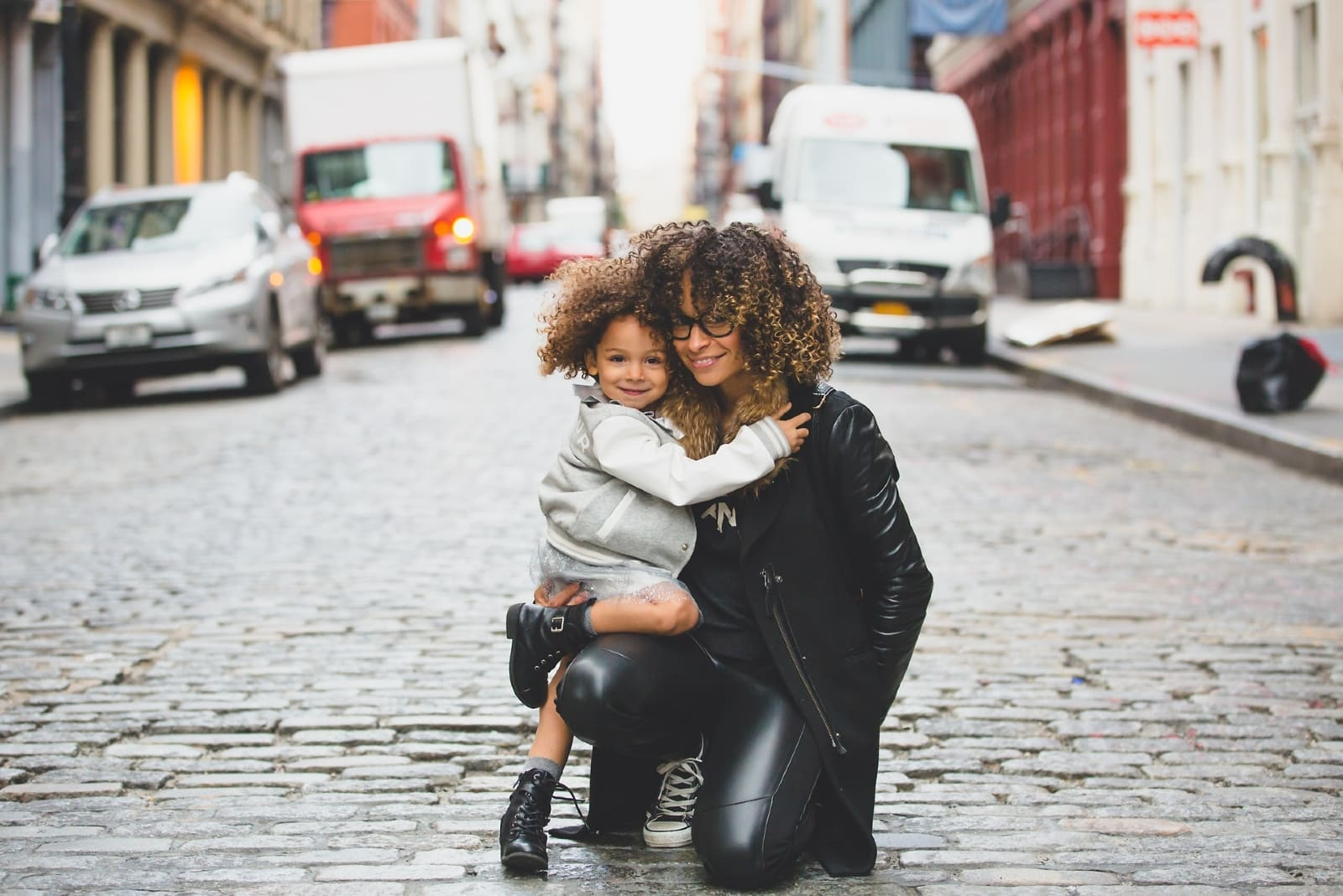 woman with curly hair holding girl on the street