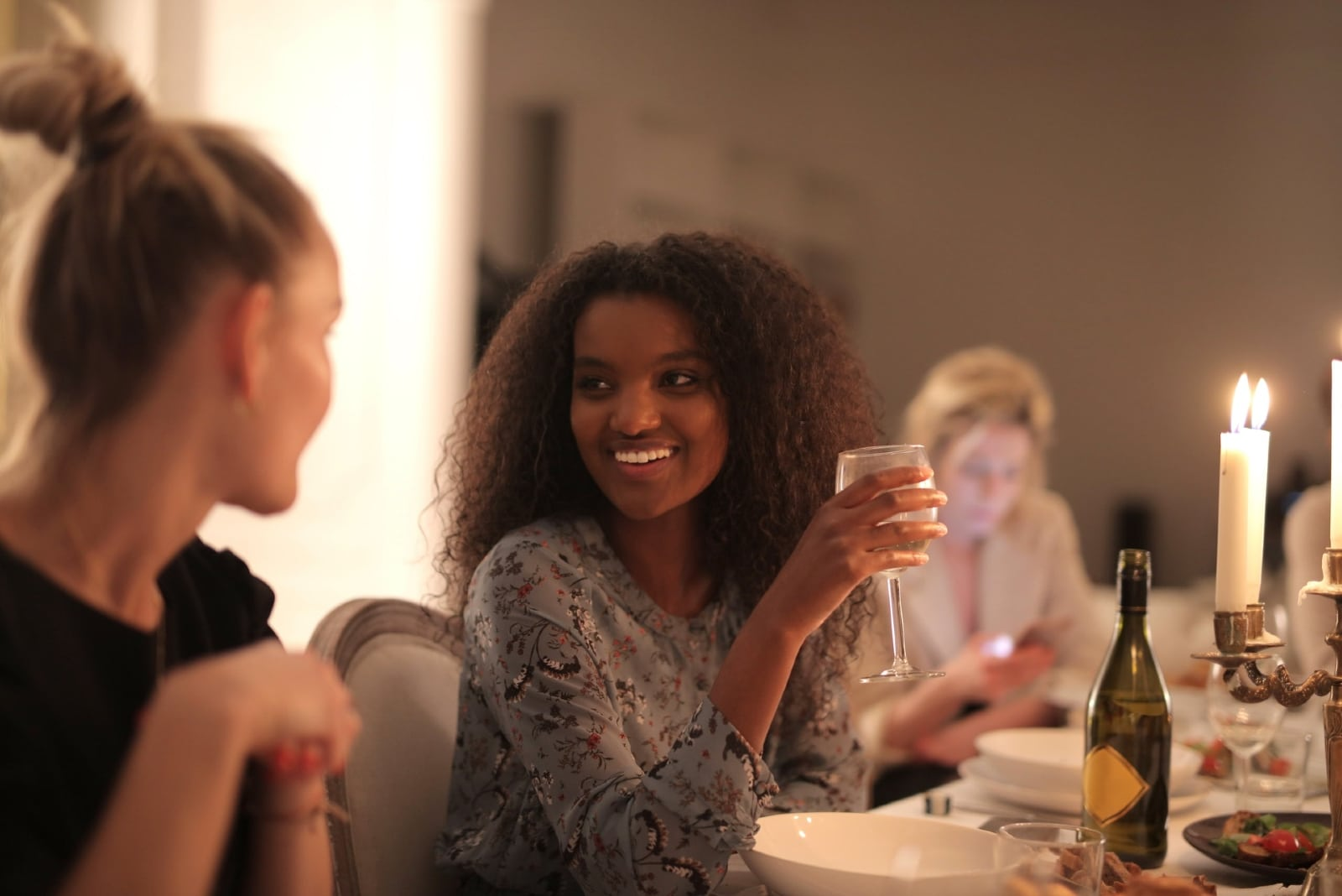 woman holding glass of wine while looking at woman