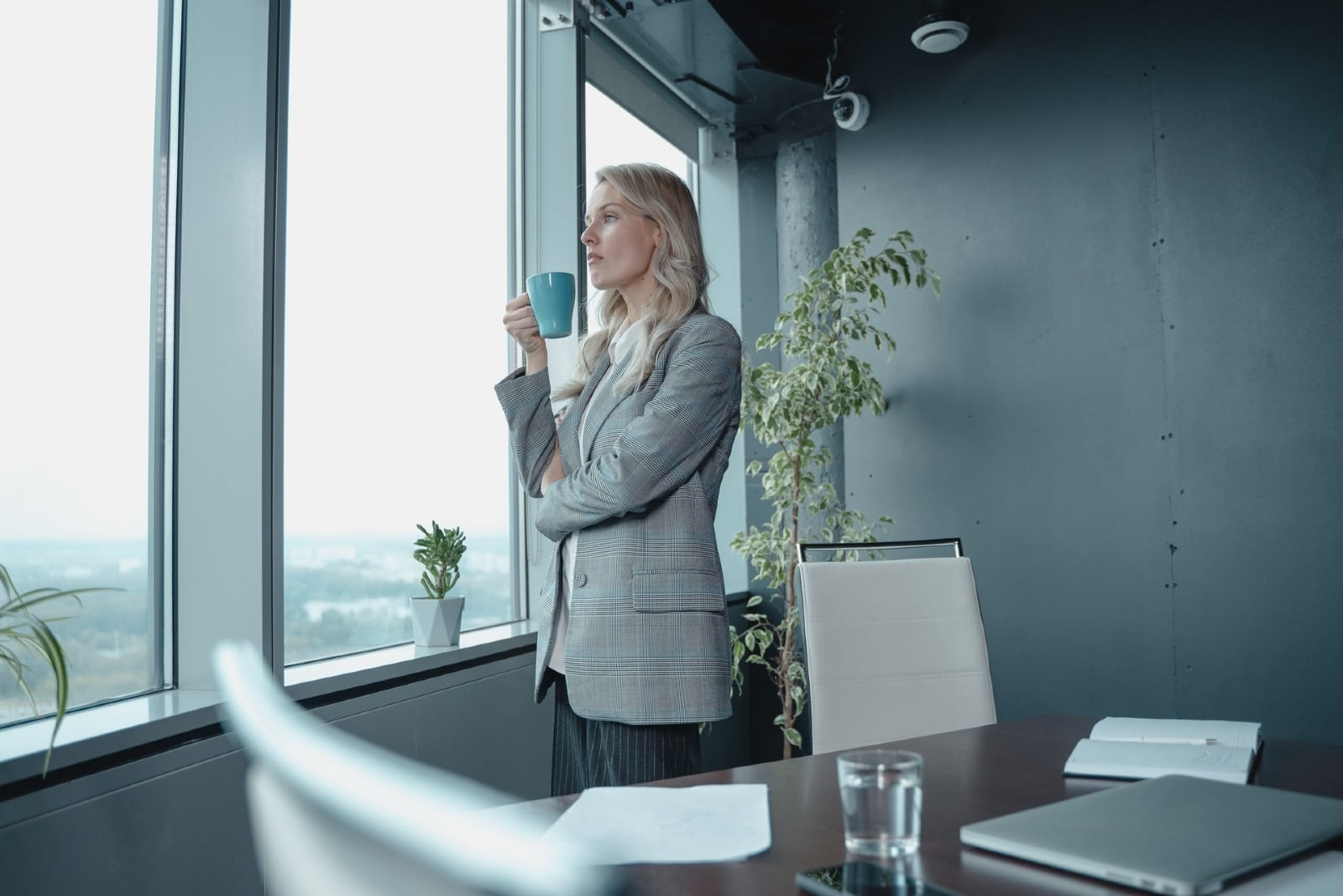 business woman holding blue mug while standing near window
