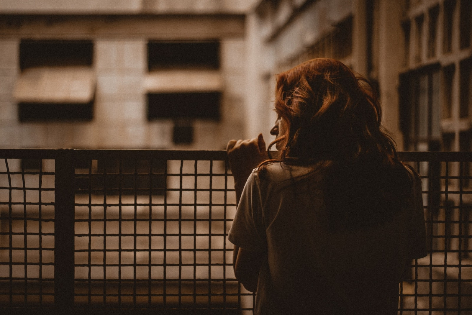 sad woman in gray t-shirt holding railings
