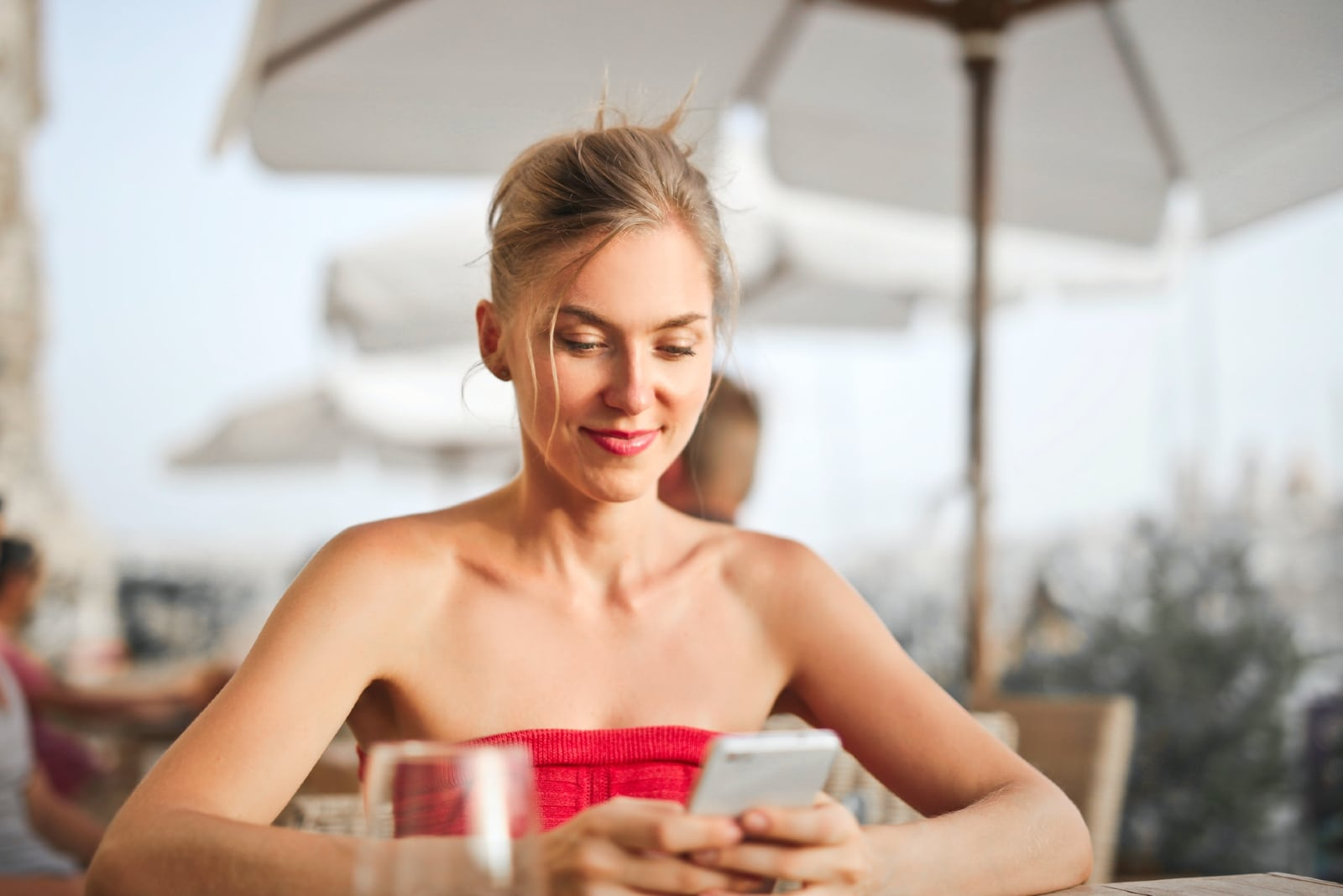 woman holding smartphone while sitting on chair