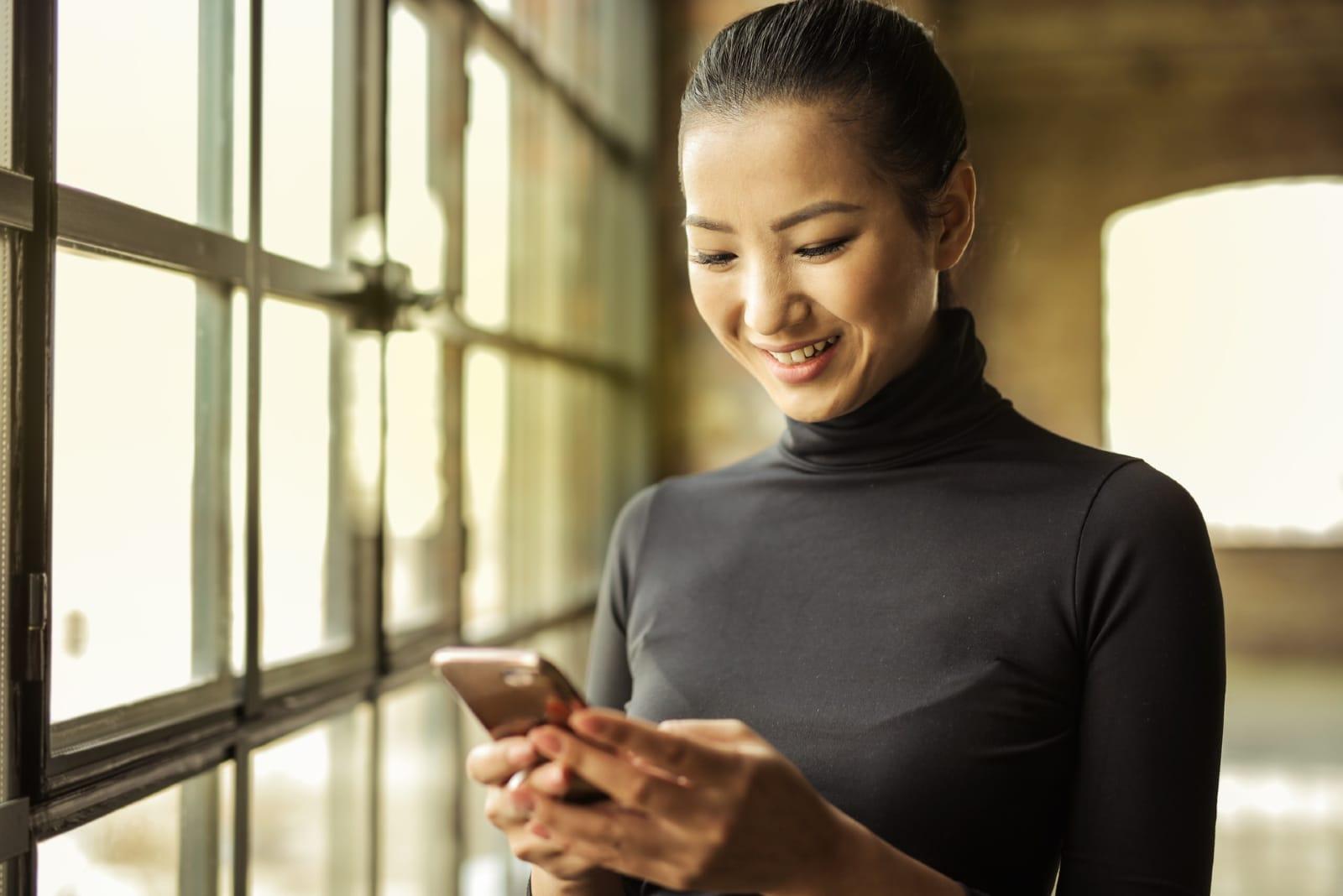 happy woman in black turtleneck holding smartphone