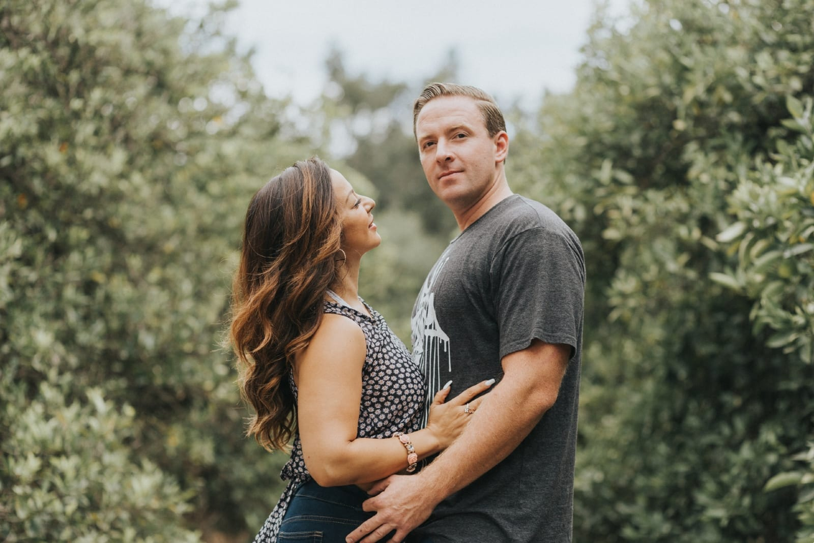 woman hugging man while standing near trees