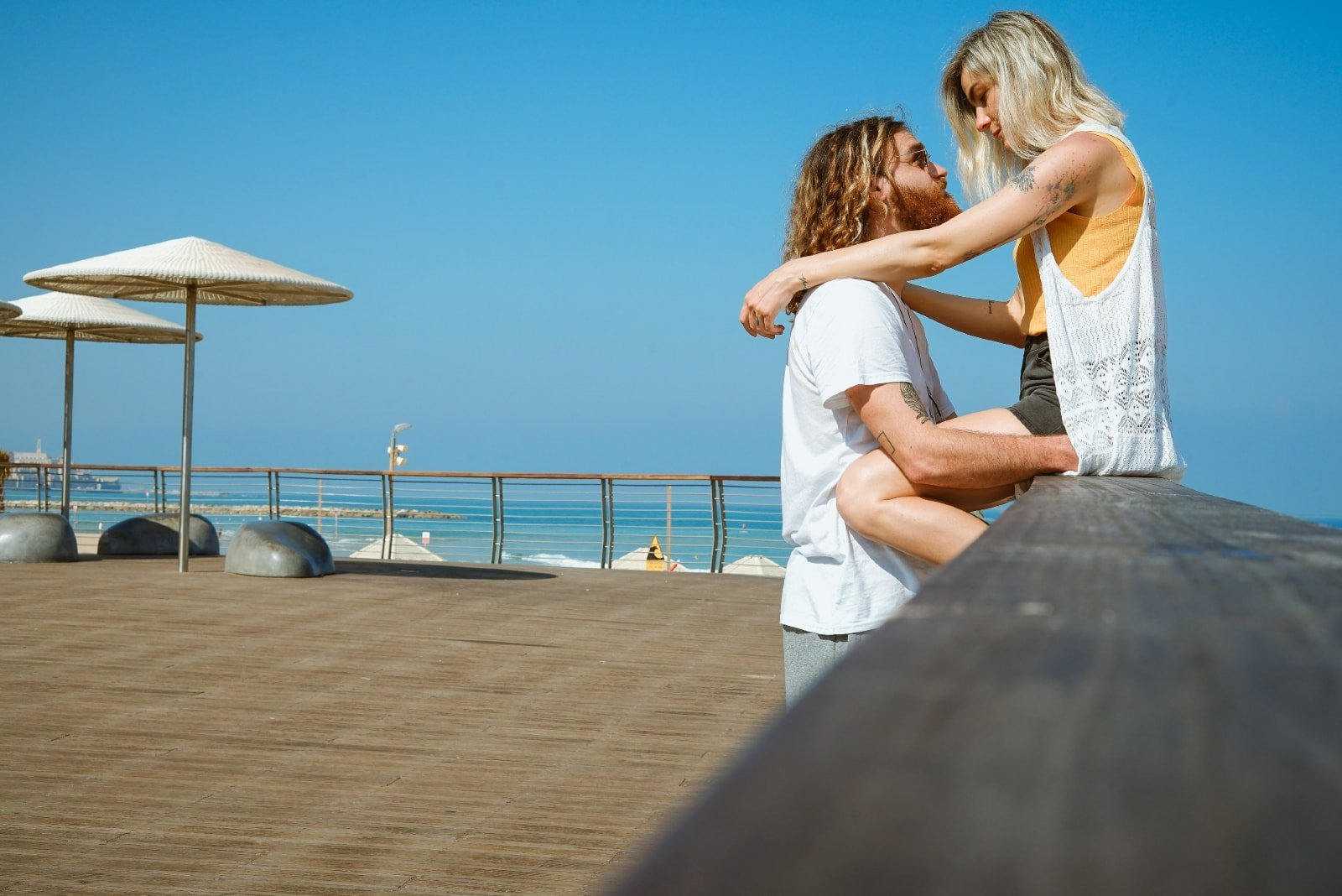 woman hugging man while sitting on brown wooden railing
