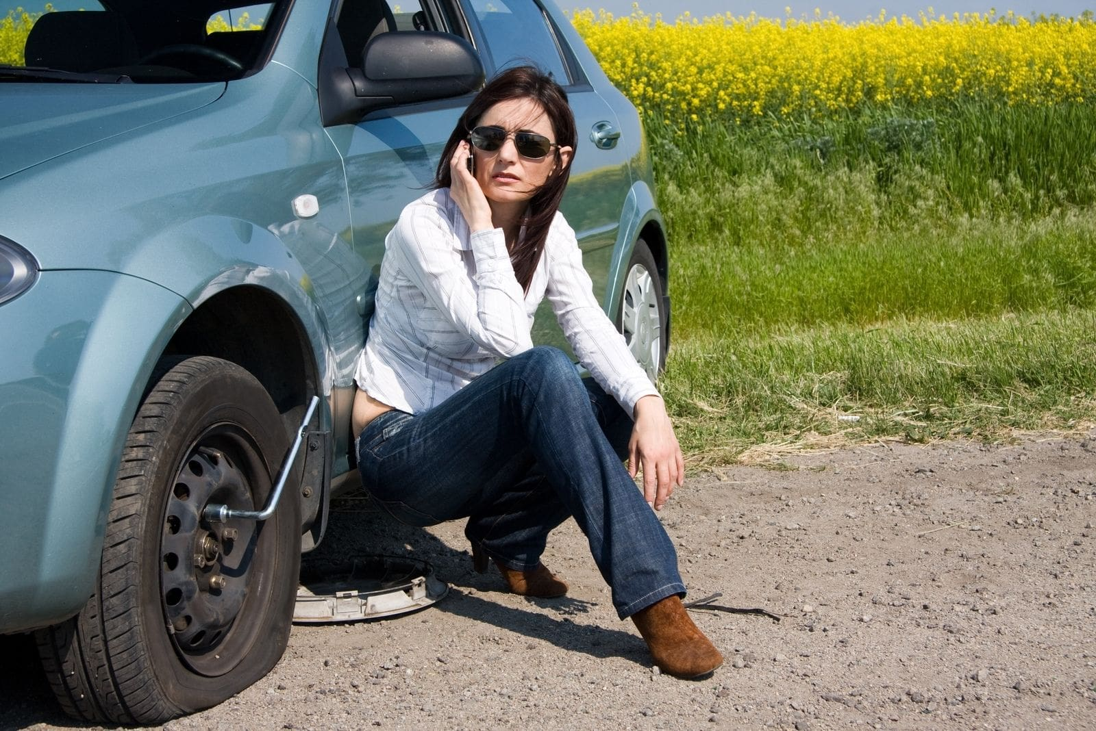 woman in distress calling sitting beside her car with broken tire