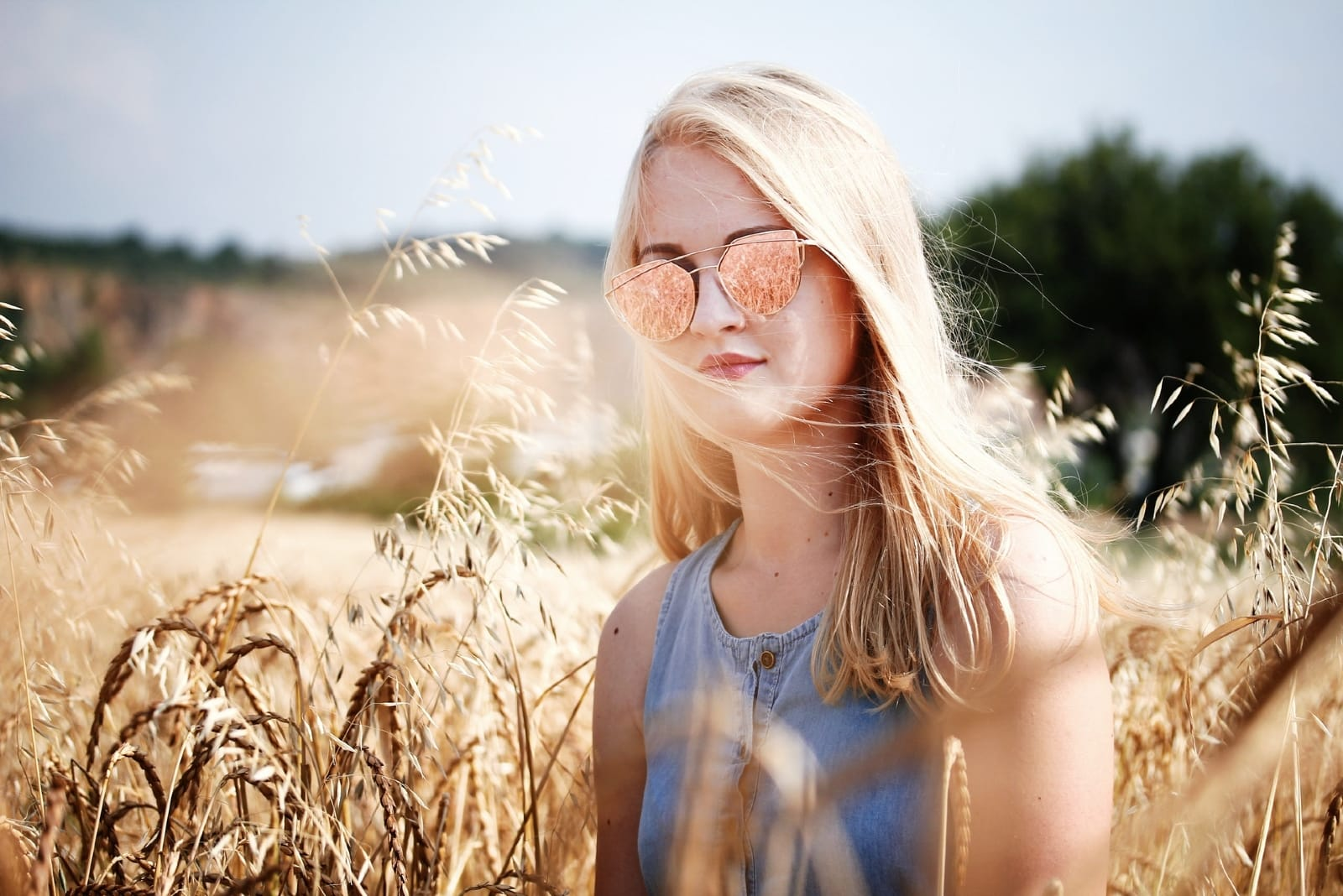 woman with sunglasses standing in wheat field