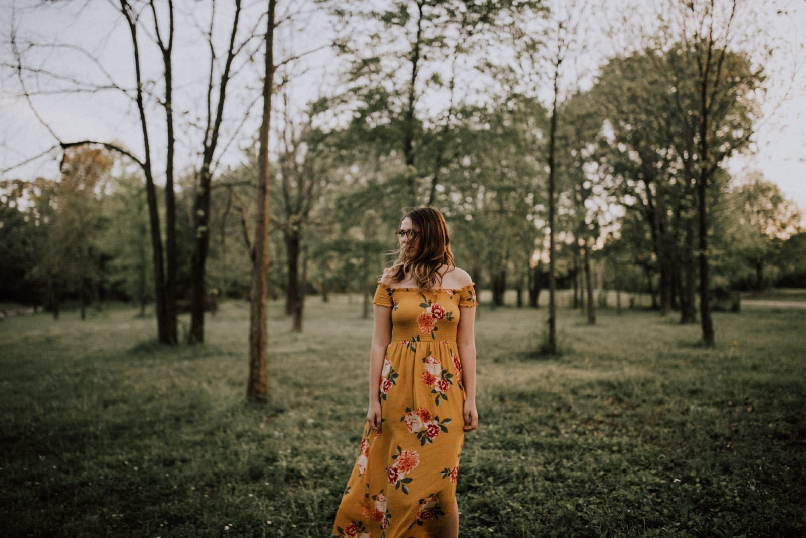 woman in yellow floral dress standing in forest