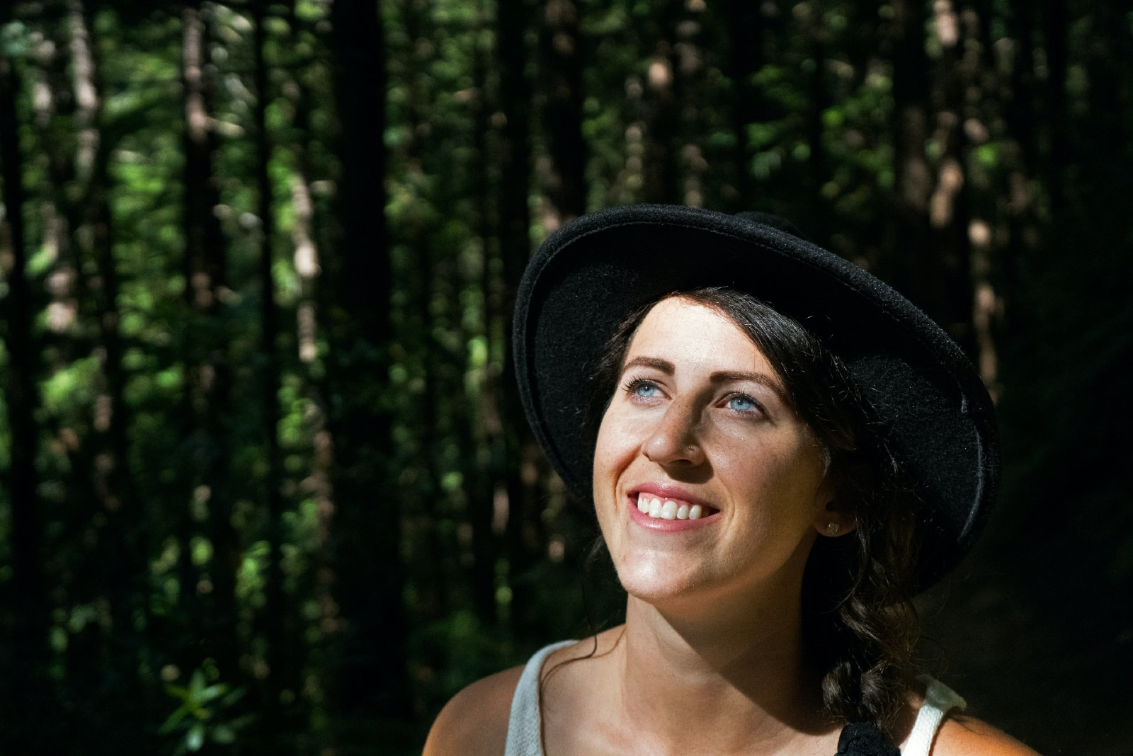 woman with black hat smiling in forest