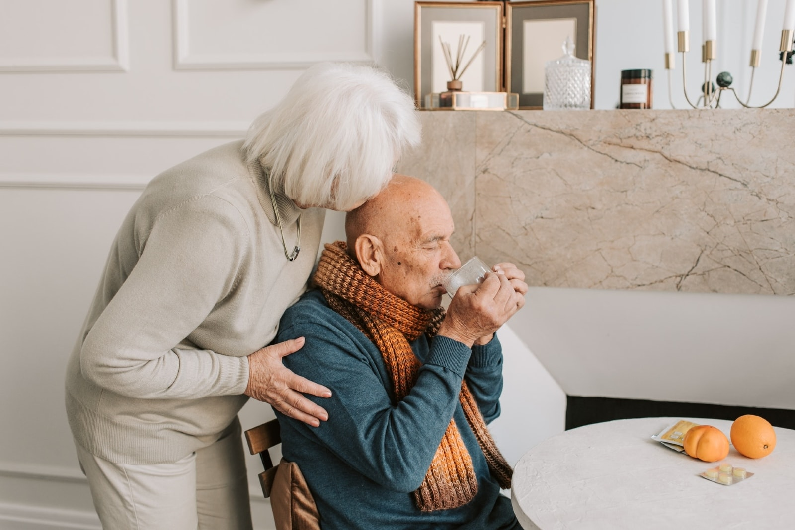 woman kissing man's head while standing indoor