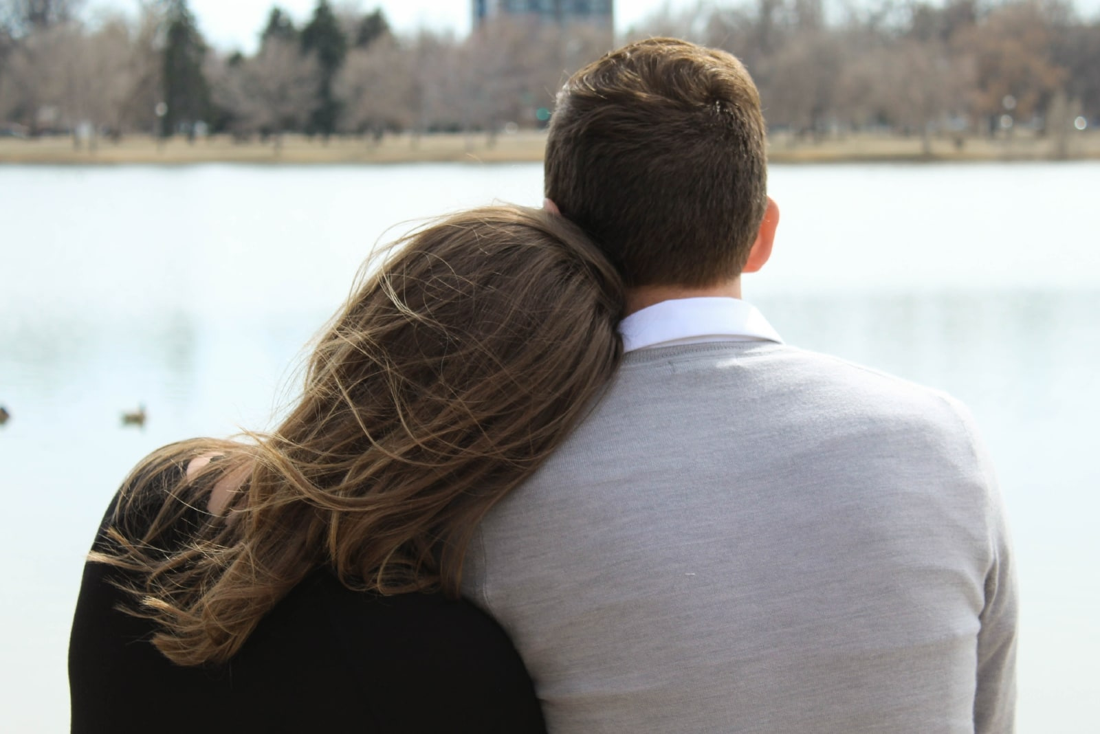 woman leaning on man's shoulder while sitting near water