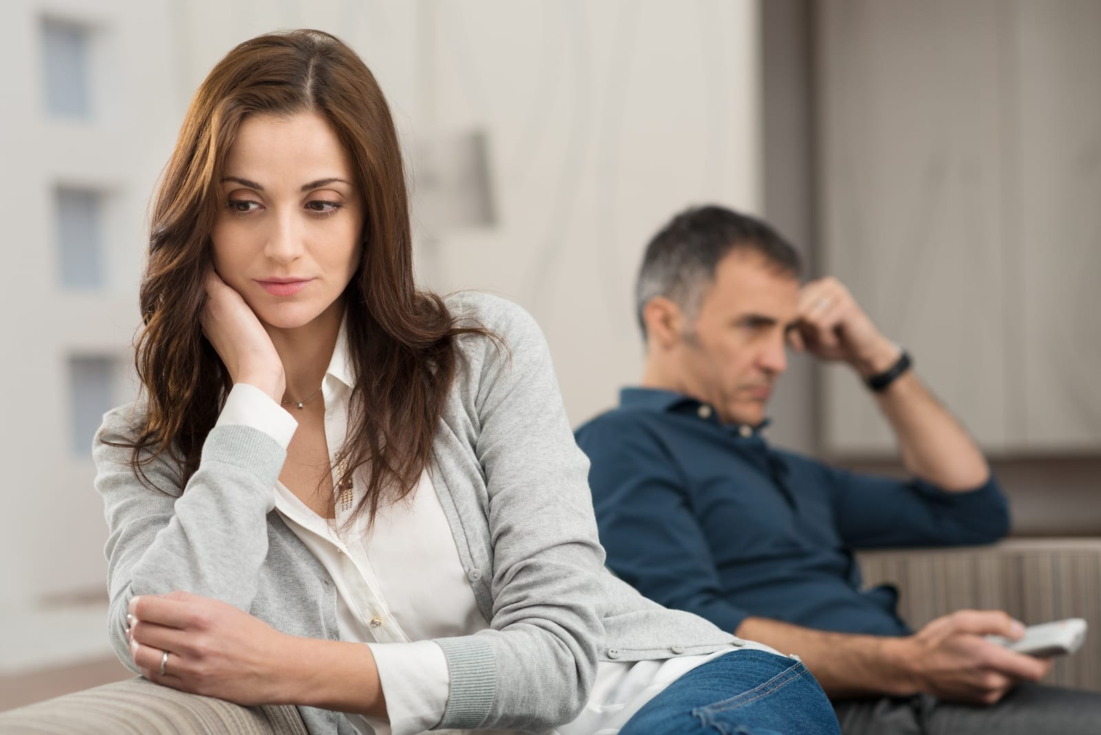 sad woman leaning on sofa while sitting near man