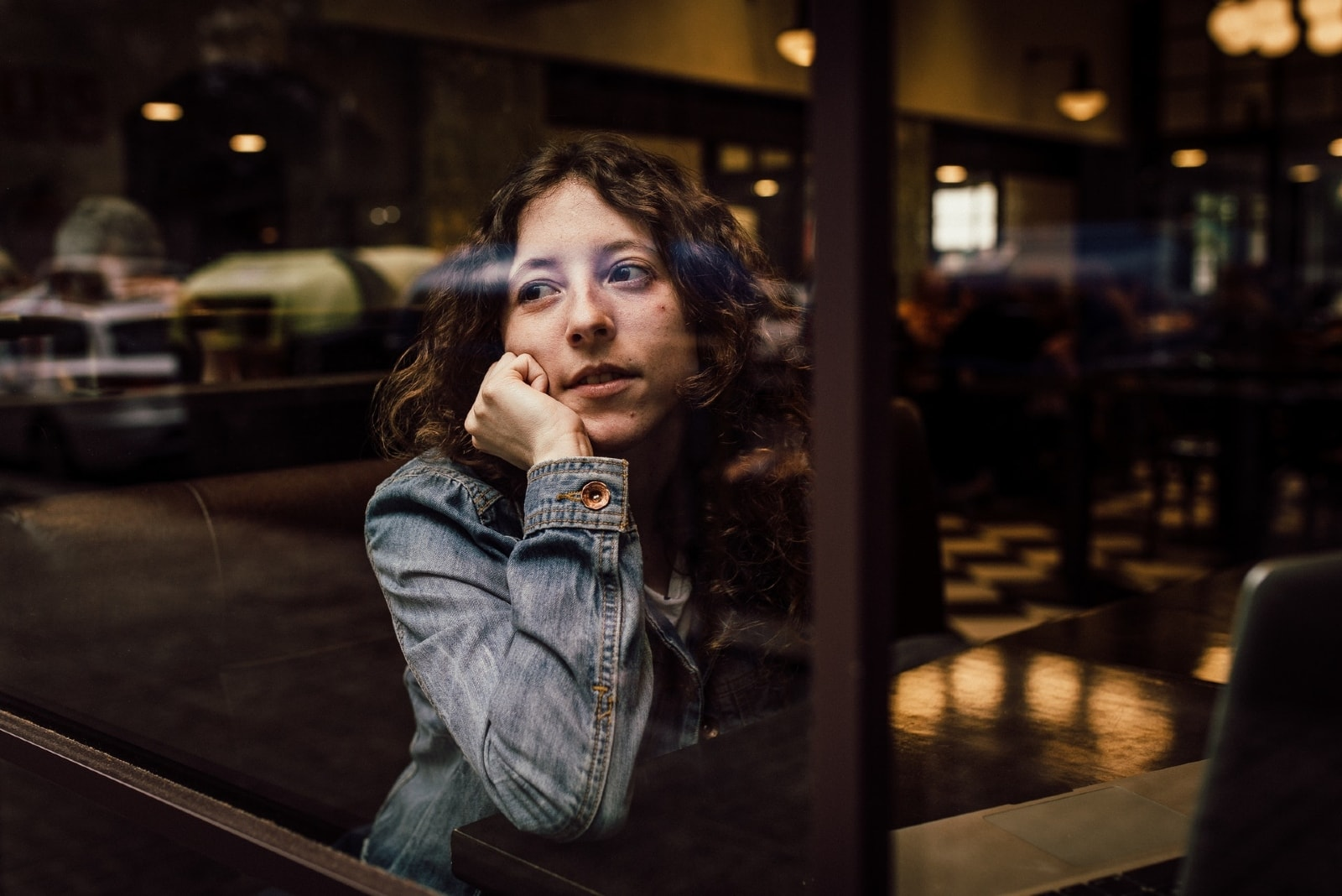 woman in denim jacket leaning on table in cafe