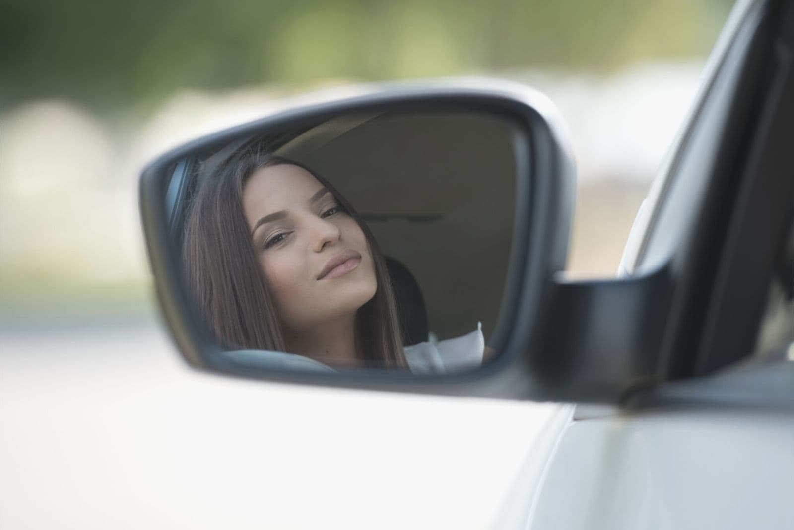 woman looking at herself in the side mirror of her car while driving