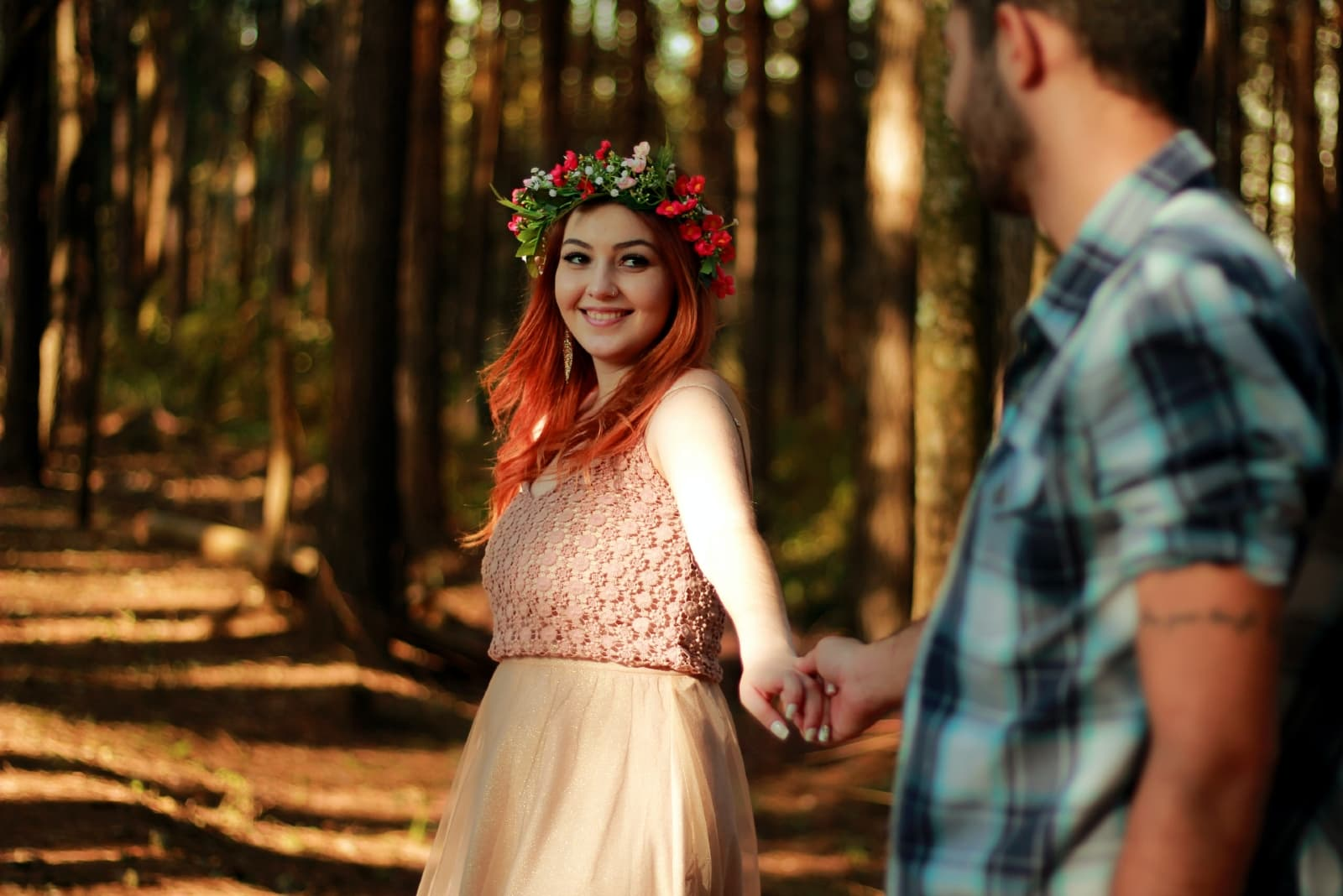 woman looking at man while standing in forest