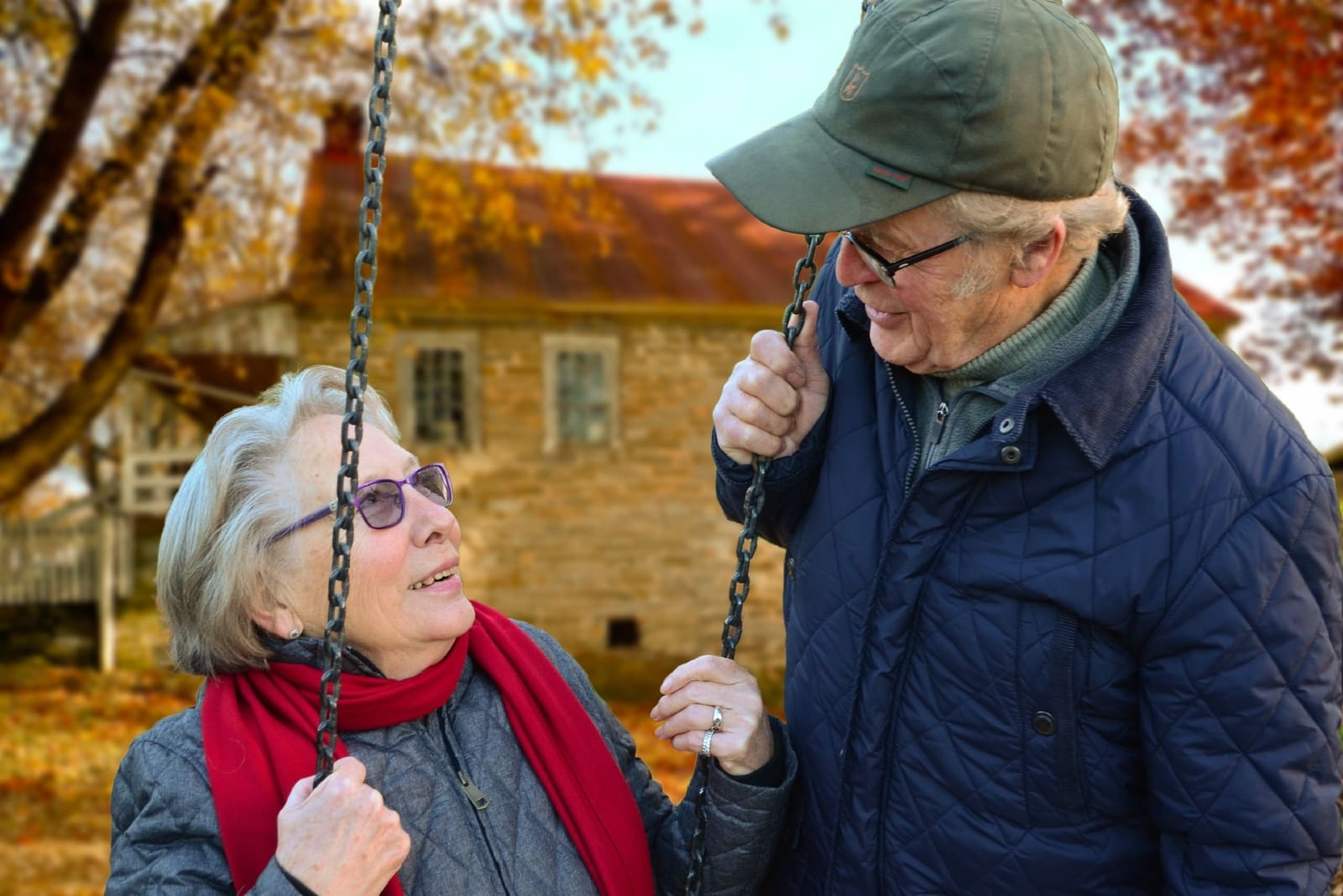 woman looking at man while sitting on swing