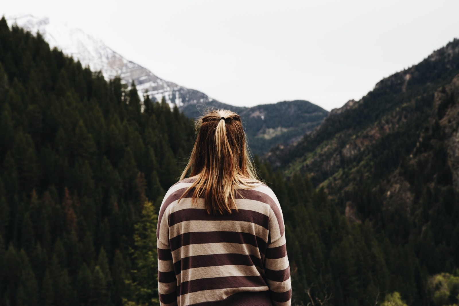 blonde woman in striped top looking at mountain
