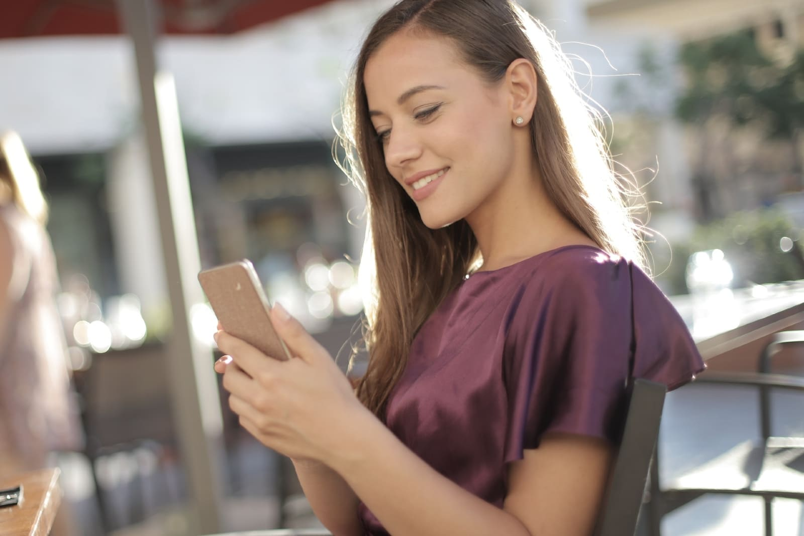 happy woman in purple blouse looking at phone