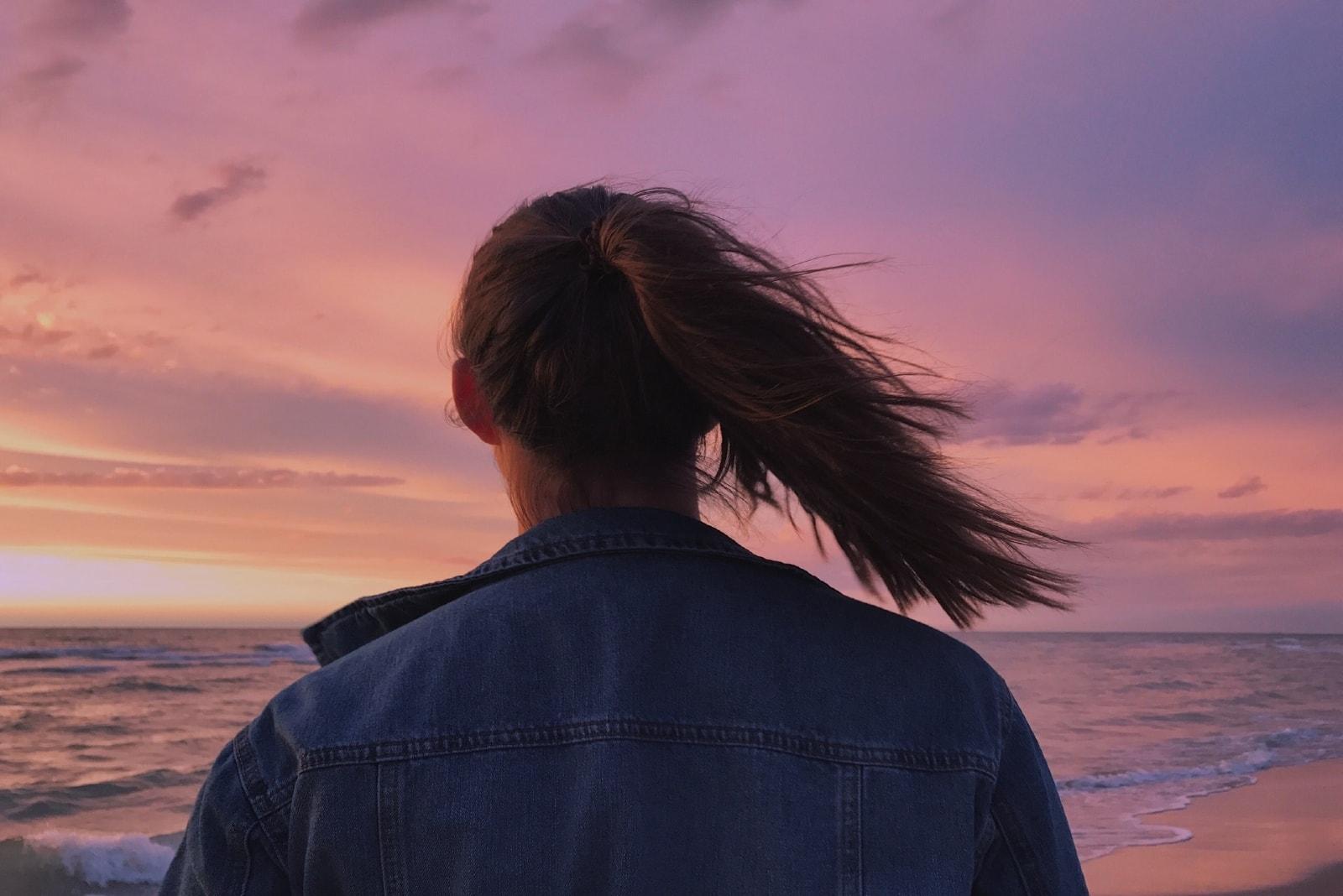 woman in denim jacket looking at sea