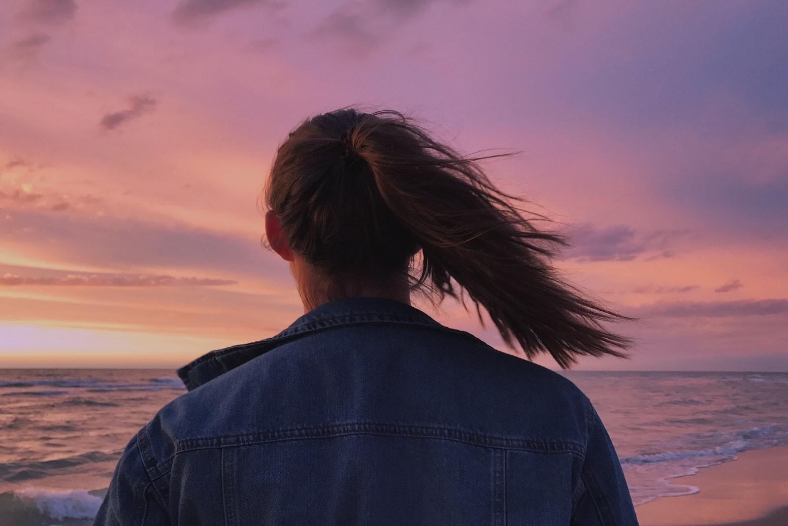 woman in denim jacket looking at sea during sunset