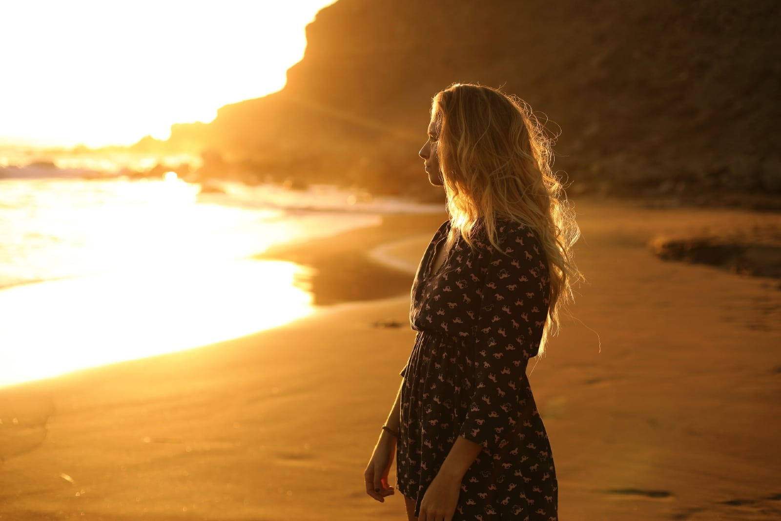 blonde woman in black printed dress looking at sea