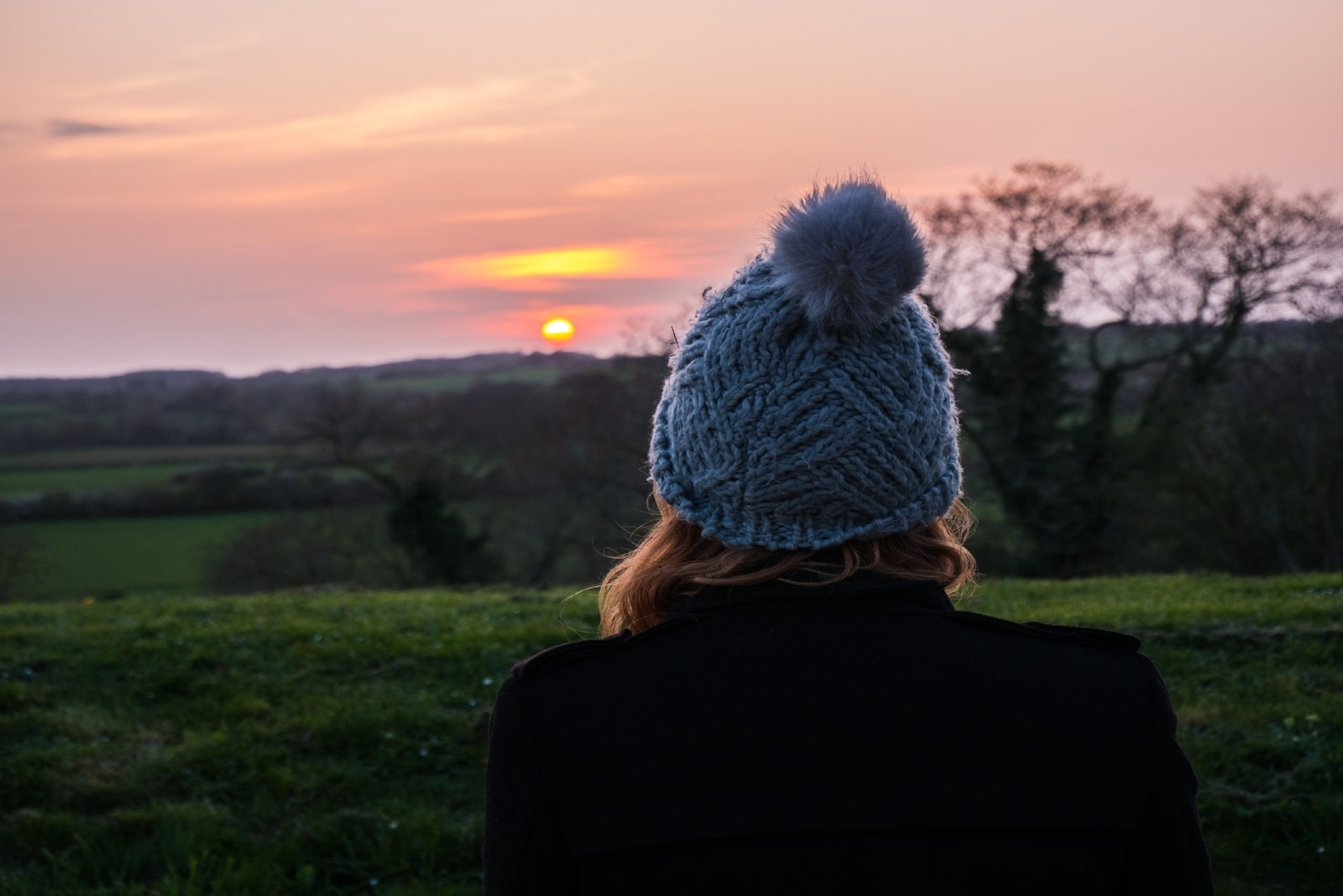 woman in blue knit cap looking at sunset