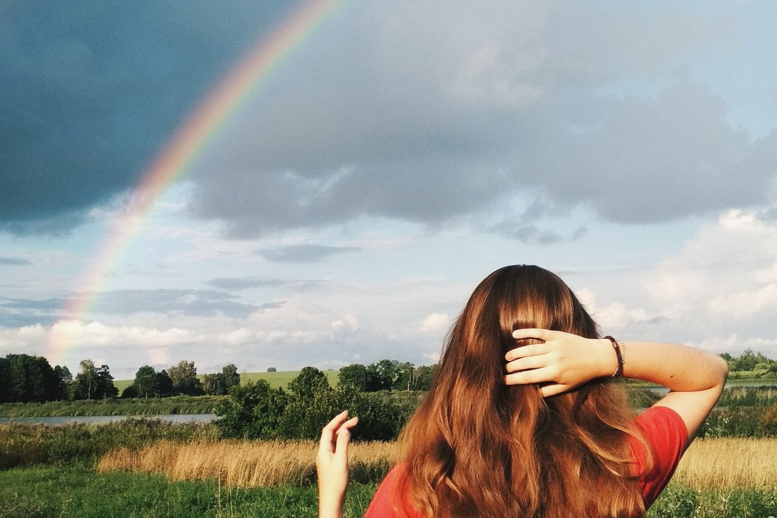 woman looking at the rainbow over the meadows while holding her hair/head