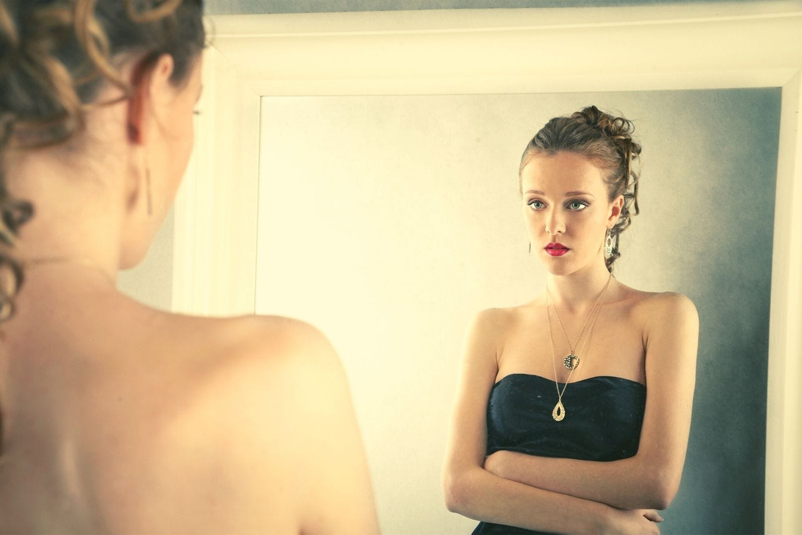 woman looking at the reflection of herself at the mirror wearing a party dress with full make up but sad