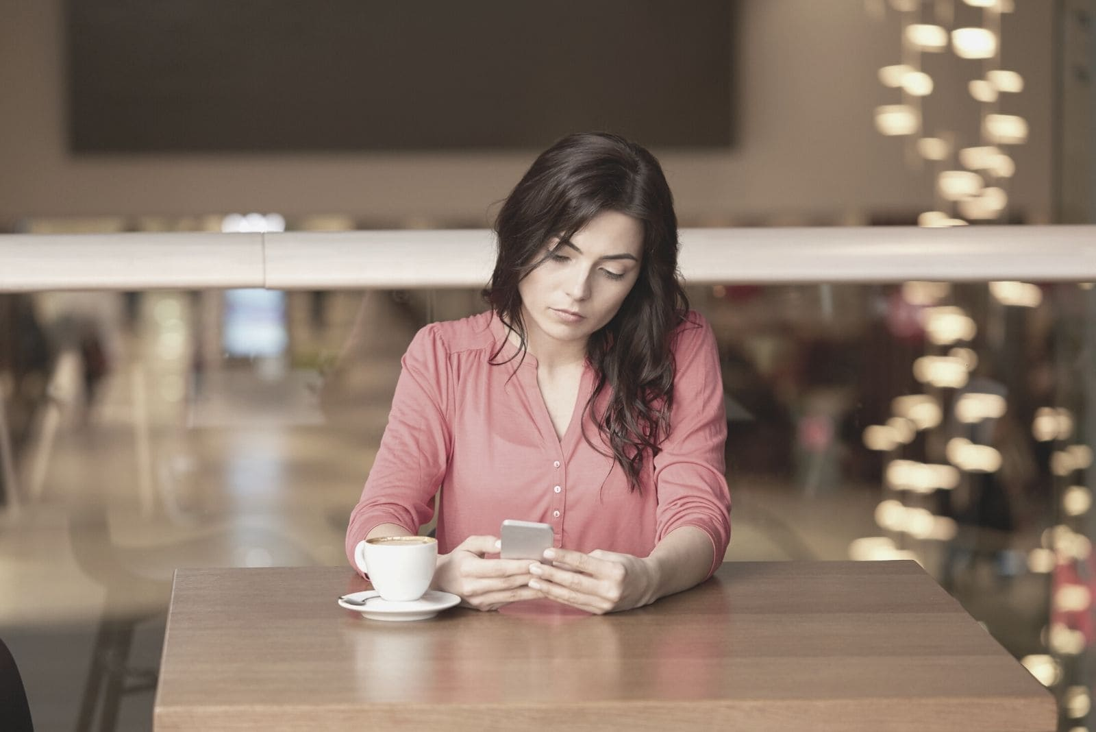 woman looking at the smartphone while having coffee at a cafe