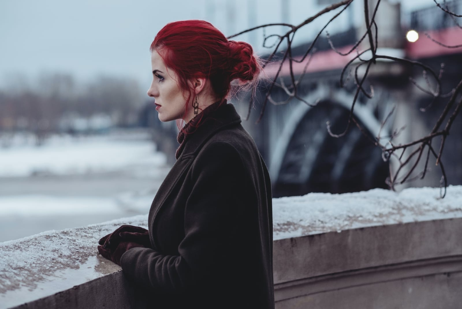 red haired woman in black coat looking at water