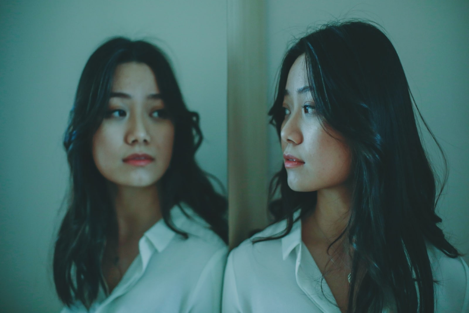 pensive woman in white shirt looking in the mirror